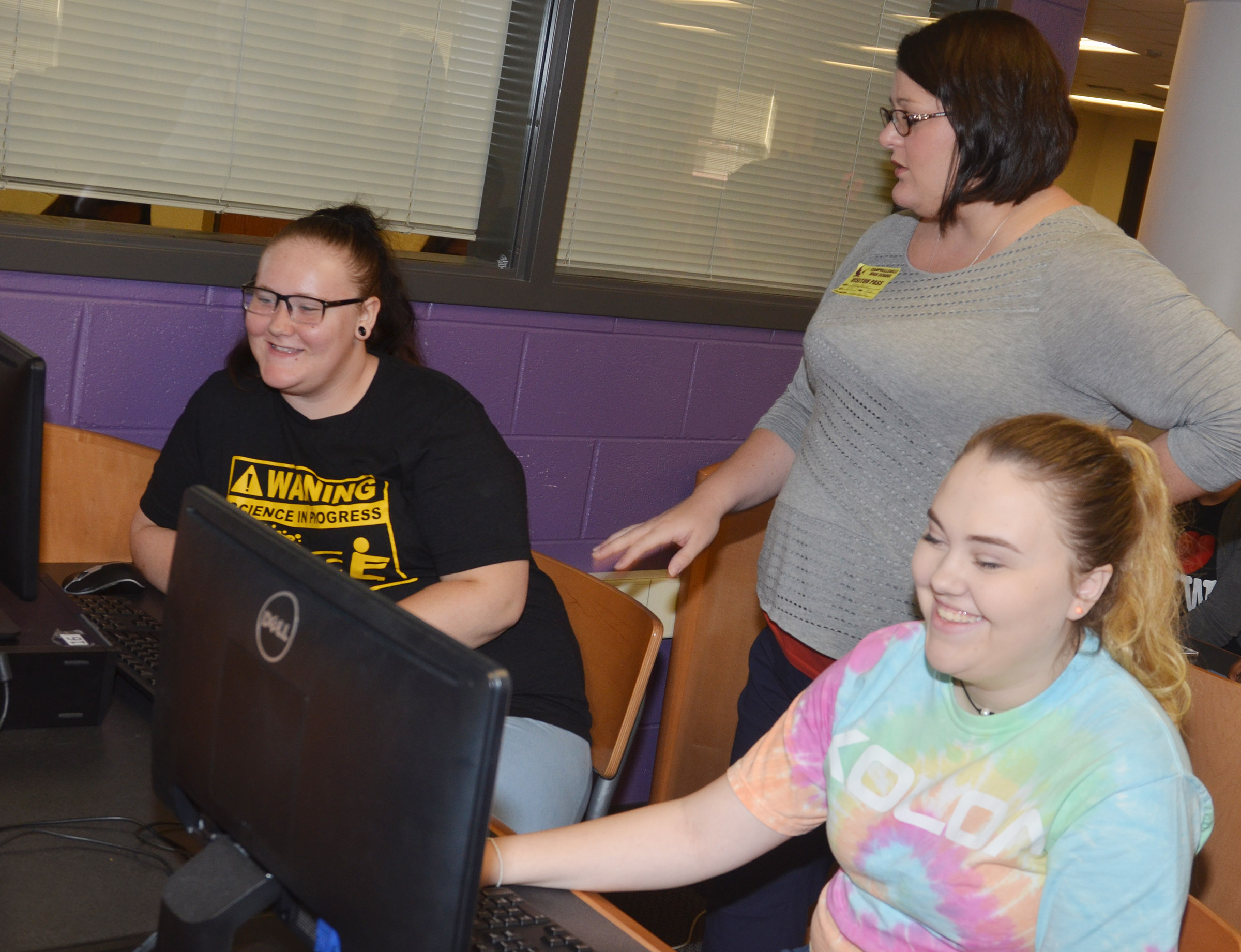 KHEAA representative Audrey Price helps CHS seniors Jay Cox, at left, and Haley Fitch as they submit their college applications.
