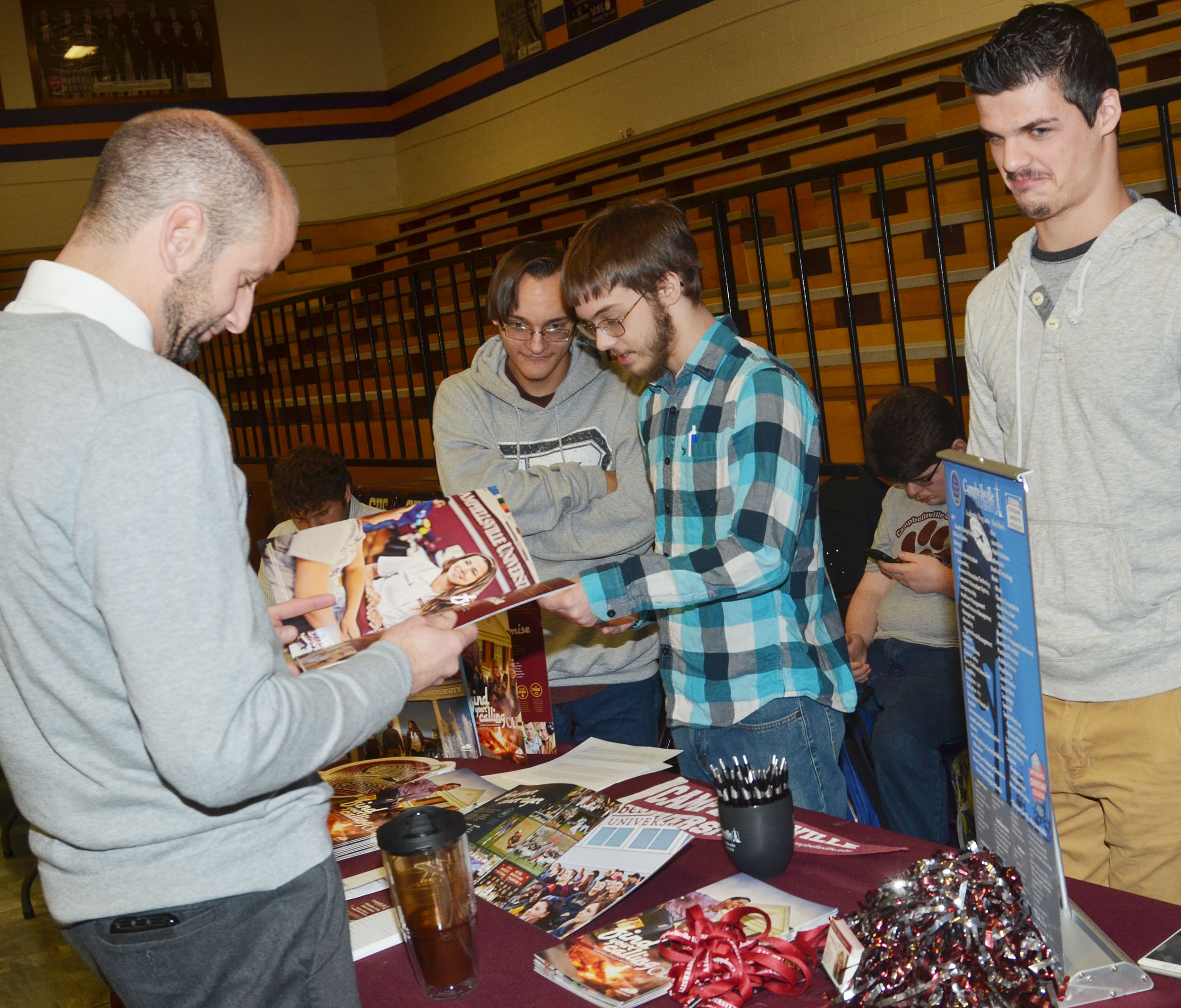 From left, CHS seniors Chase Atwood, Gabriel Clark and Stone Williams present information about Campbellsville University.
