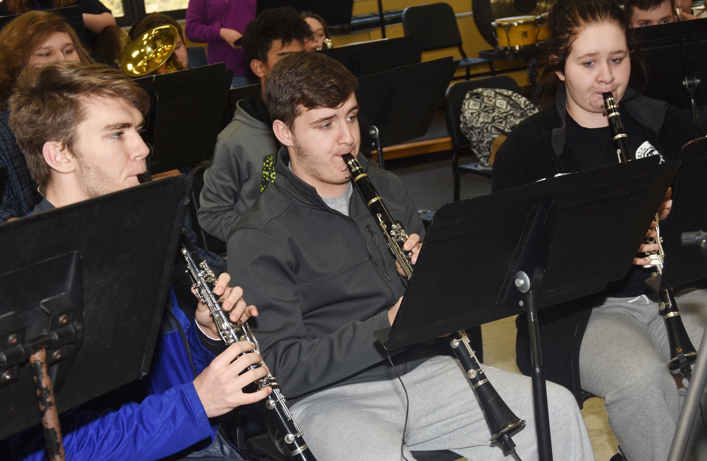 From left, seniors Christian Berry and Austin Fitzgerald and junior Leslie McKenzie play clarinet during a rehearsal for KMEA concert band assessment.
