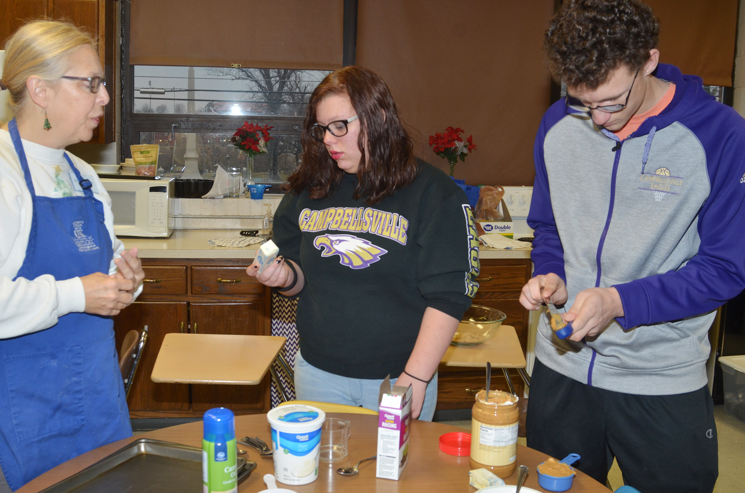 Angie Freeman, expanded foods and nutrition program assistant at Taylor County Extension Office, helps CHS freshmen Hannah Hall and Brennon Wheeler measure their ingredients.