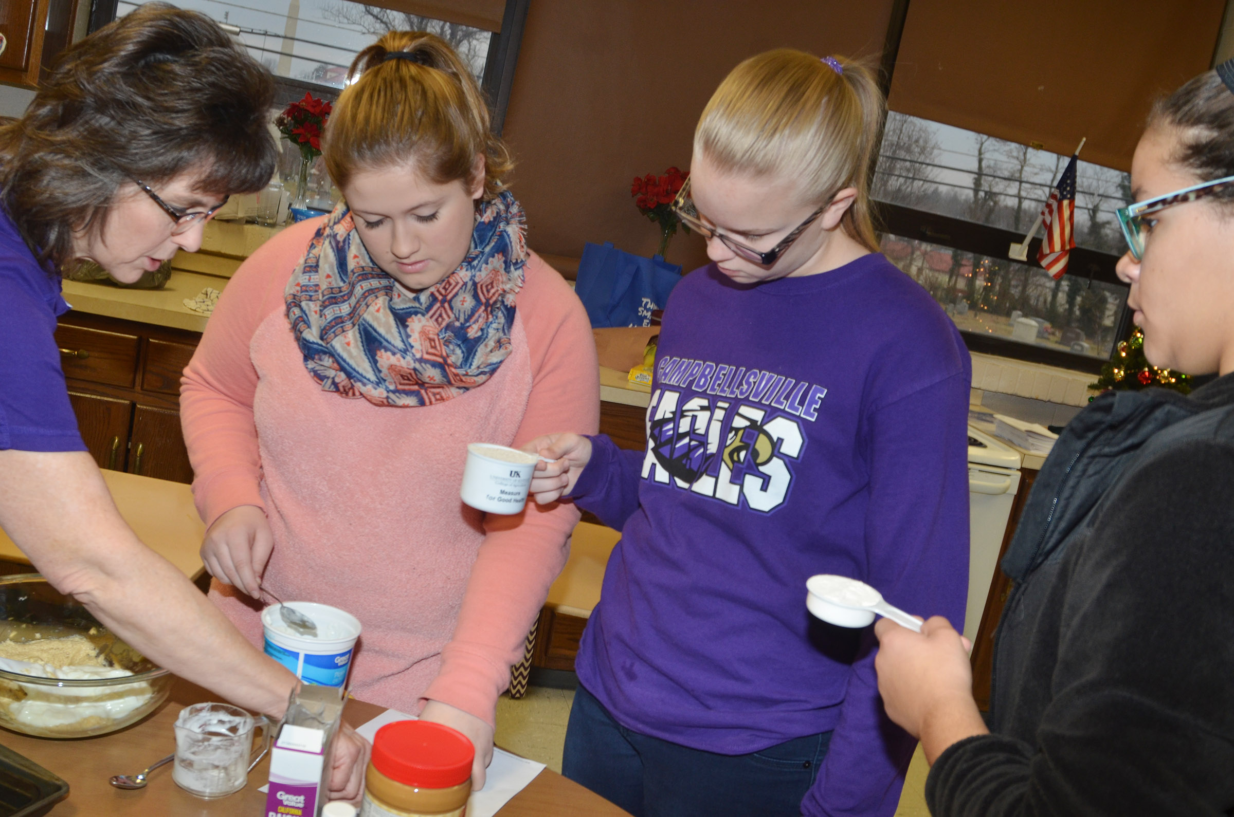 CHS teacher Deanna Campbell, at left, helps freshmen, from left, Aleah Knifley, Tahler Franklin and Taliyah Hazelwood measure ingredients for banana oat cookies.