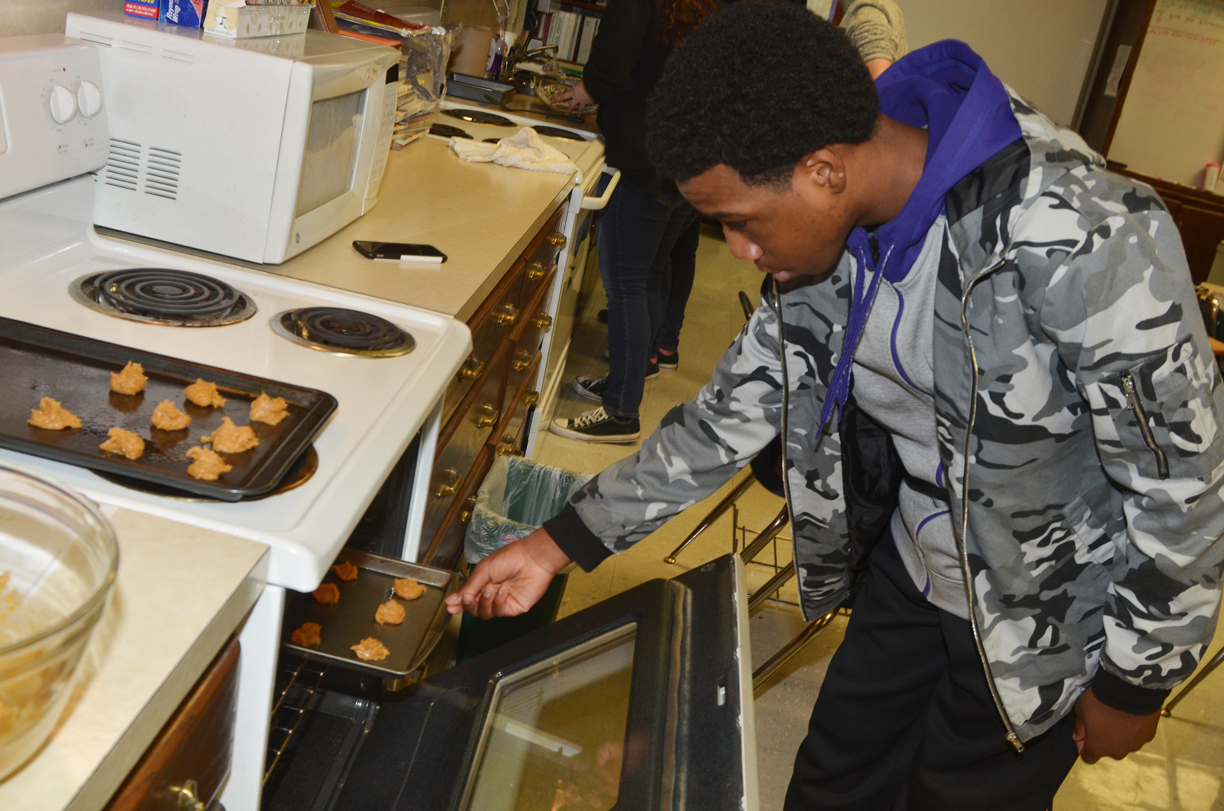 CHS freshman Malachi Corley places his group's peanut butter cookies in the oven.