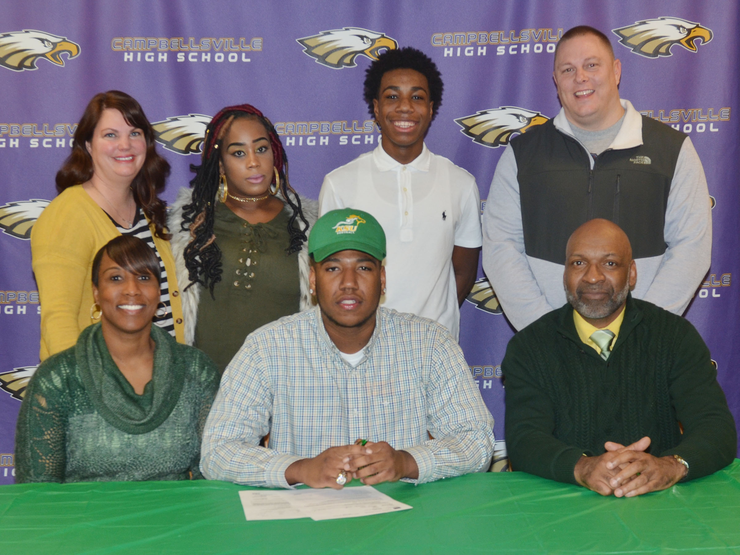 "CHS seniors Micah Corley and Arick Groves will continue their academic and football careers at Kentucky State University this fall. The two signed their letters of intent in a special ceremony on Monday, Feb. 6. Attending the ceremony with Corley, front, center, are, in front, his mother Latonya Bridgewater and his step-father Wilando ""Chop"" Bridgewater. Back, his godmother Karrie Lee, his sister De'Erricka Corley, his brother Malachi Corley, a CHS freshmen, and his godfather Robert Lee."
