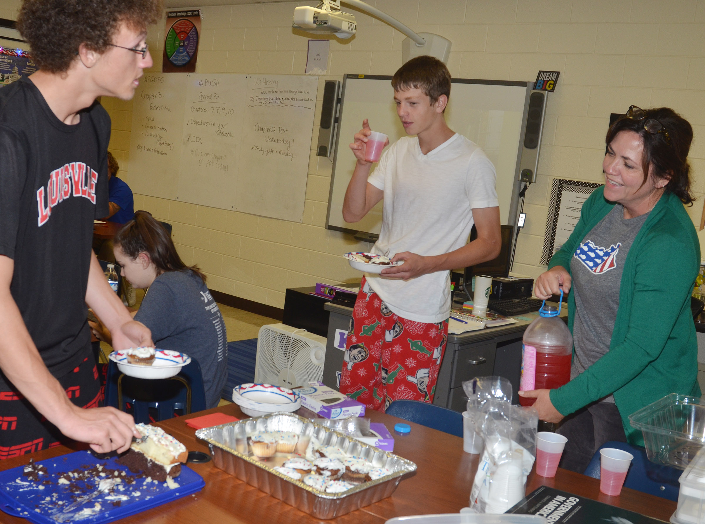 CES teacher Susan Dabney serves her students Brennon Wheeler, at left, and Noah Hughes, sophomores, marble cake cupcakes and layer cake during their Constitution Day party.