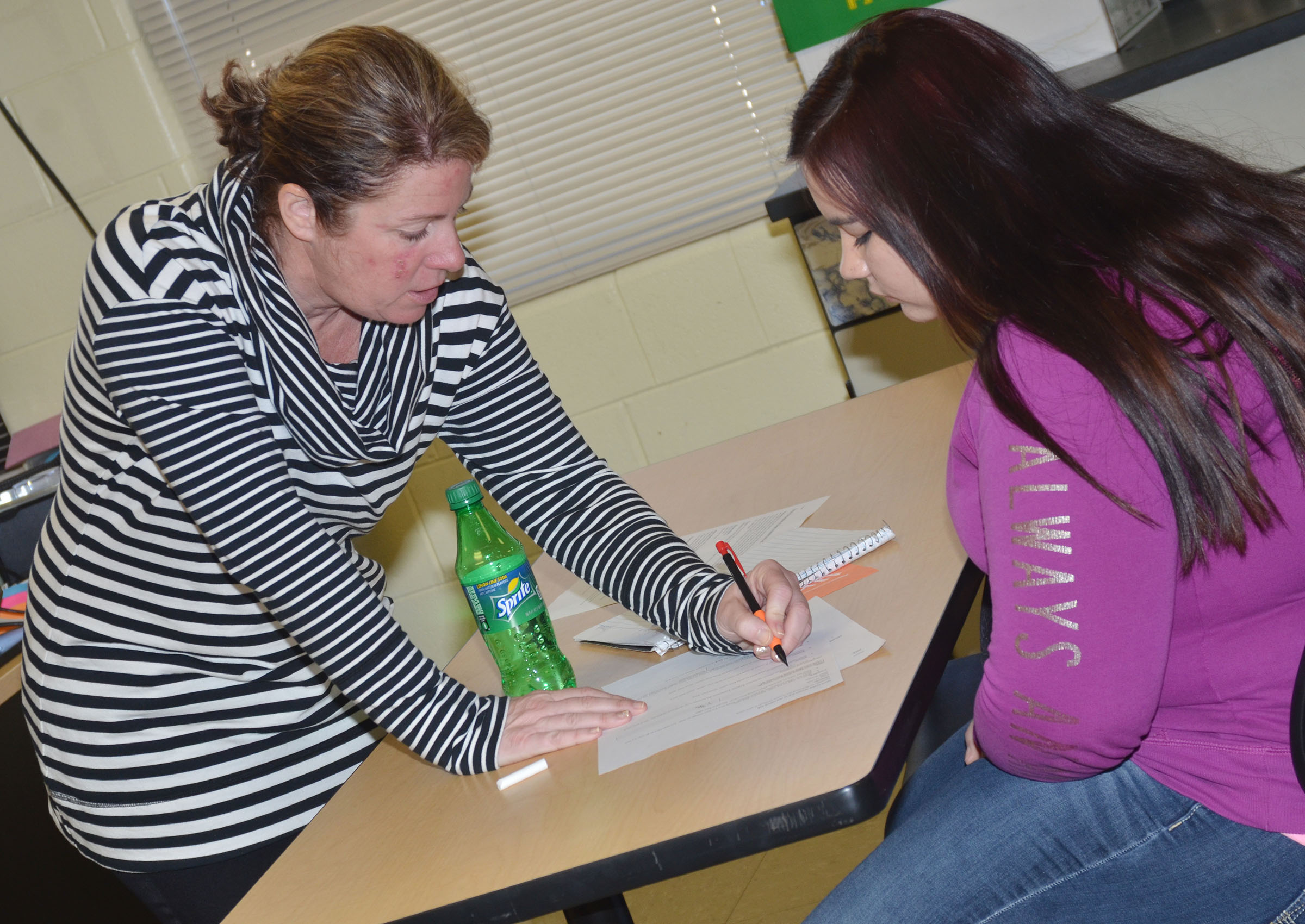 CHS teacher Dee Doss helps junior Darah Troxell perform her calculations.