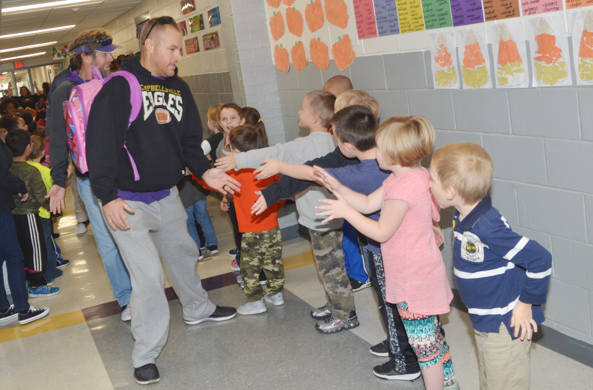 CHS assistant football coach Robbie Gribbins high-fives CES kindergarteners.