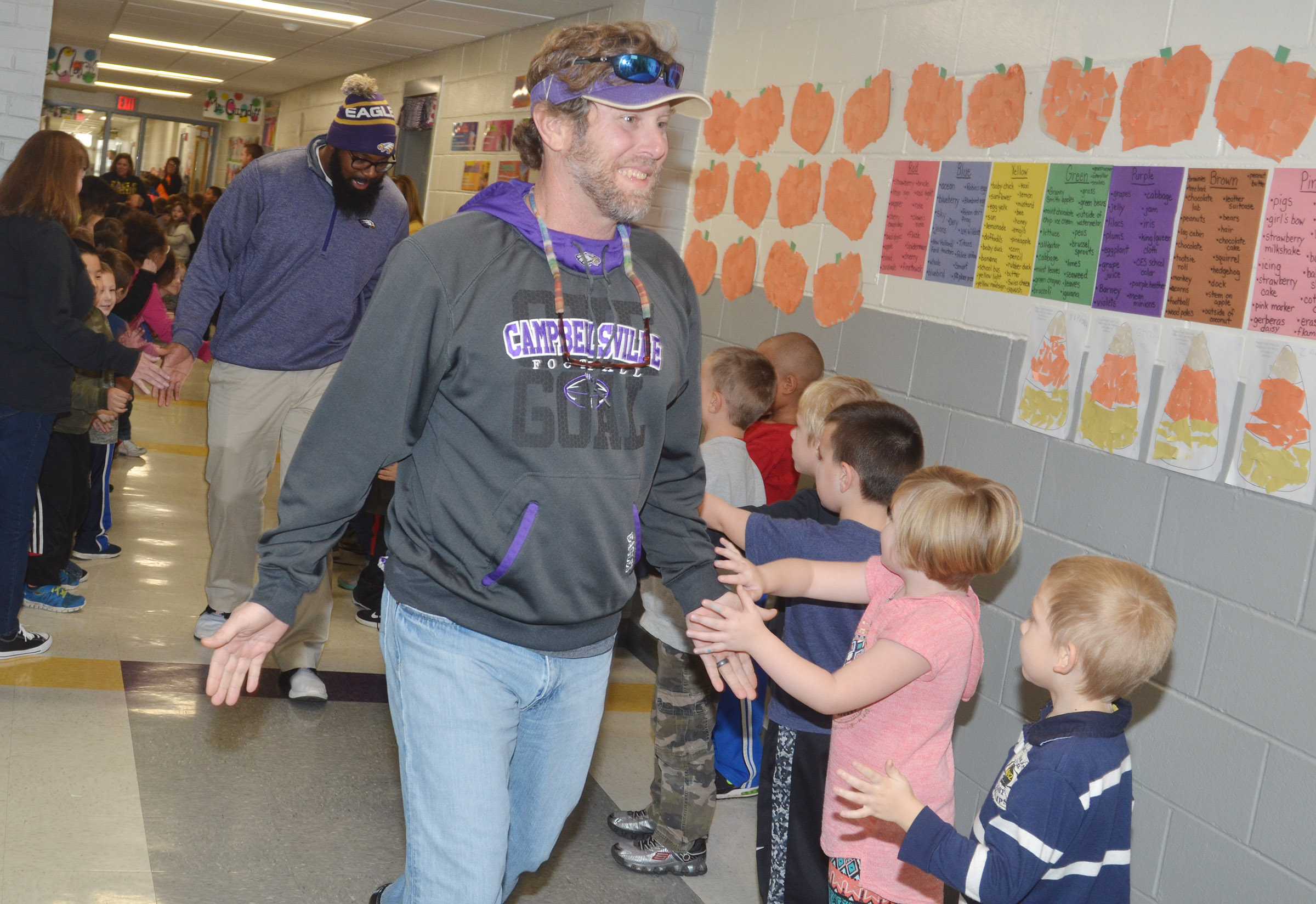CHS assistant football coach Herb Wiseman high-fives CES kindergarteners.