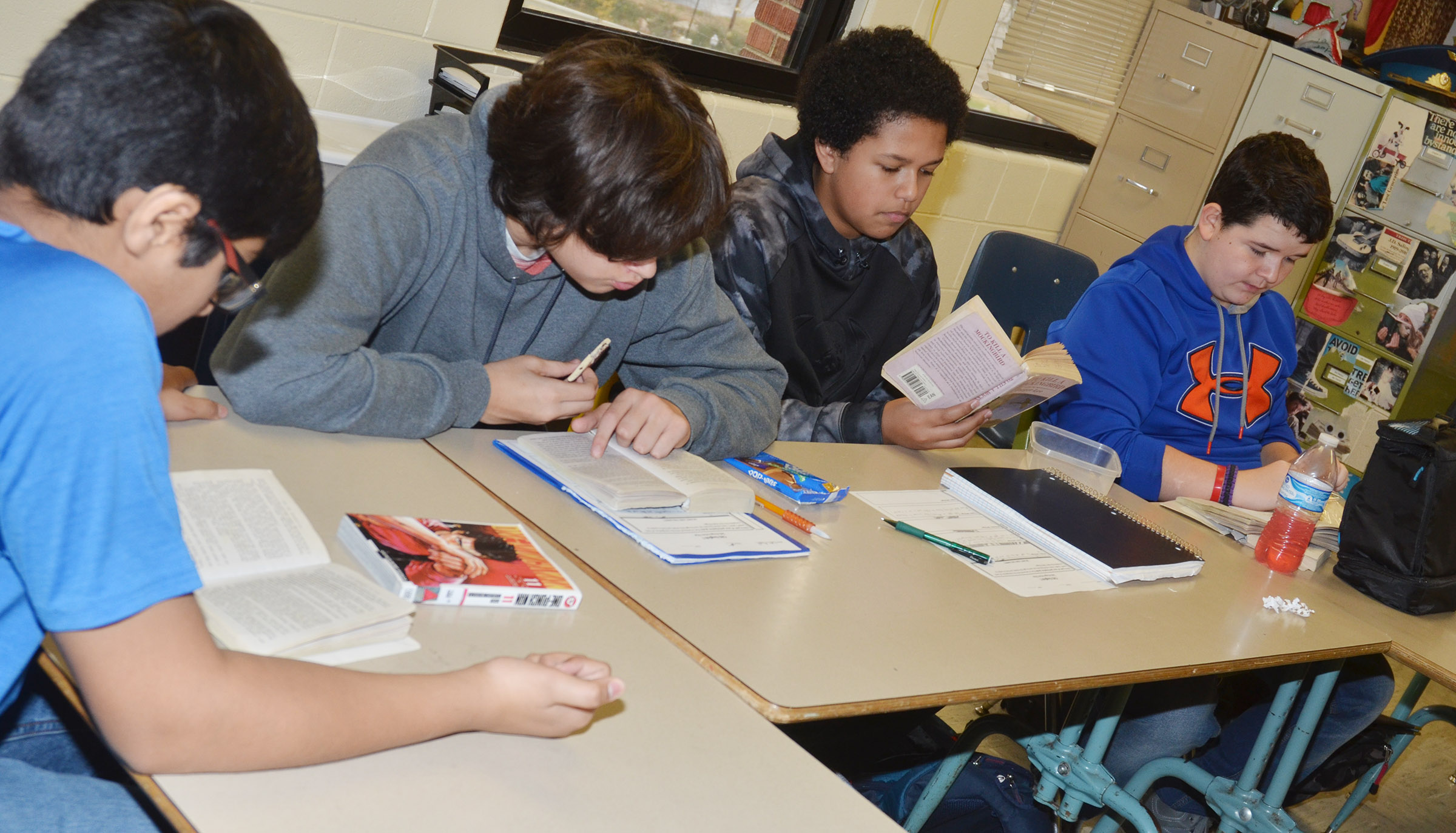 "From left, Campbellsville Middle School eighth-graders Yash Patel, Nate Arachi, Tezon Mitchell and Adin Hunt follow along as teacher Tyler Hardy reads ""To Kill A Mockingbird."""