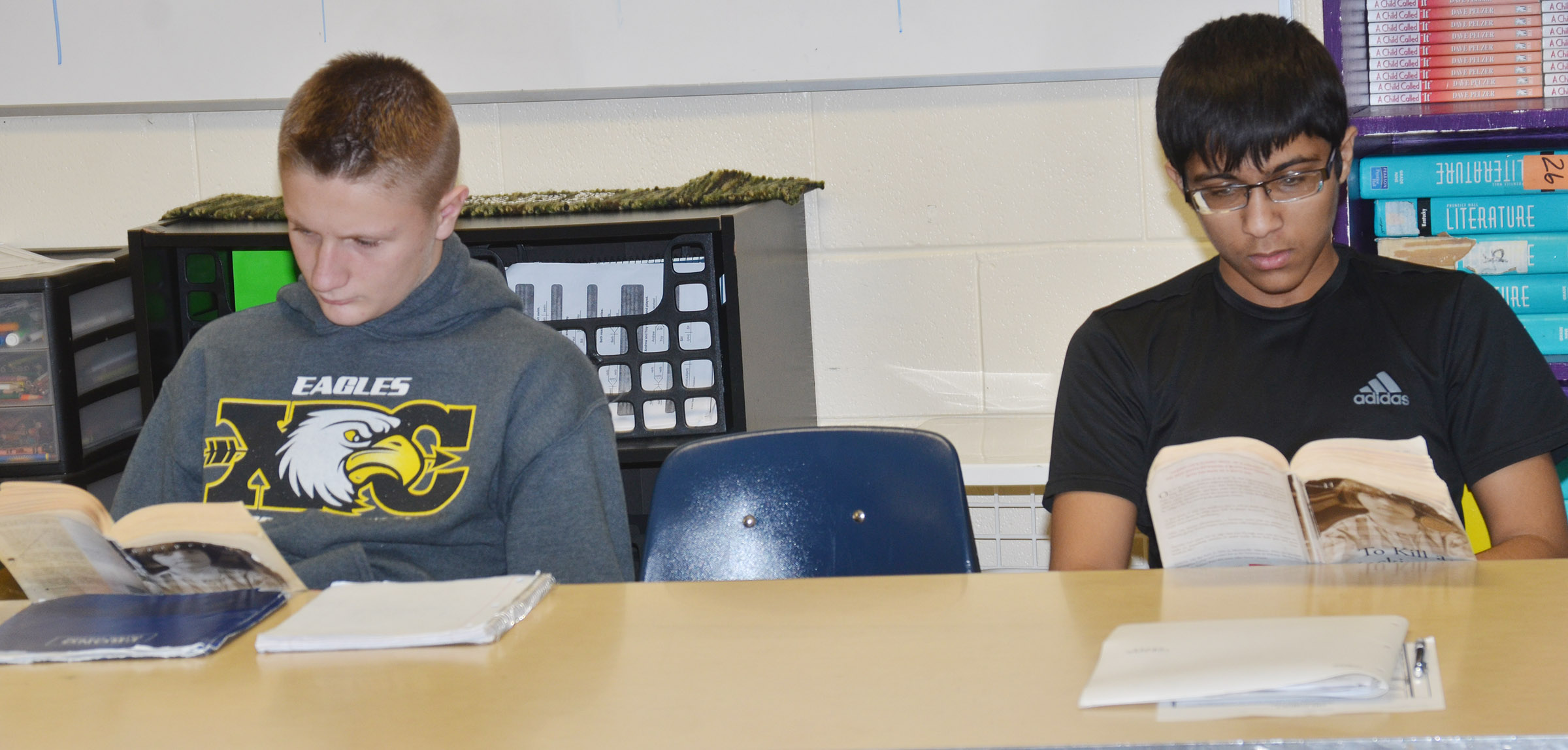 "CHS freshmen Jake Dicken, at left, and Raj Patel follow along as teacher Tyler Hardy reads ""To Kill A Mockingbird."""