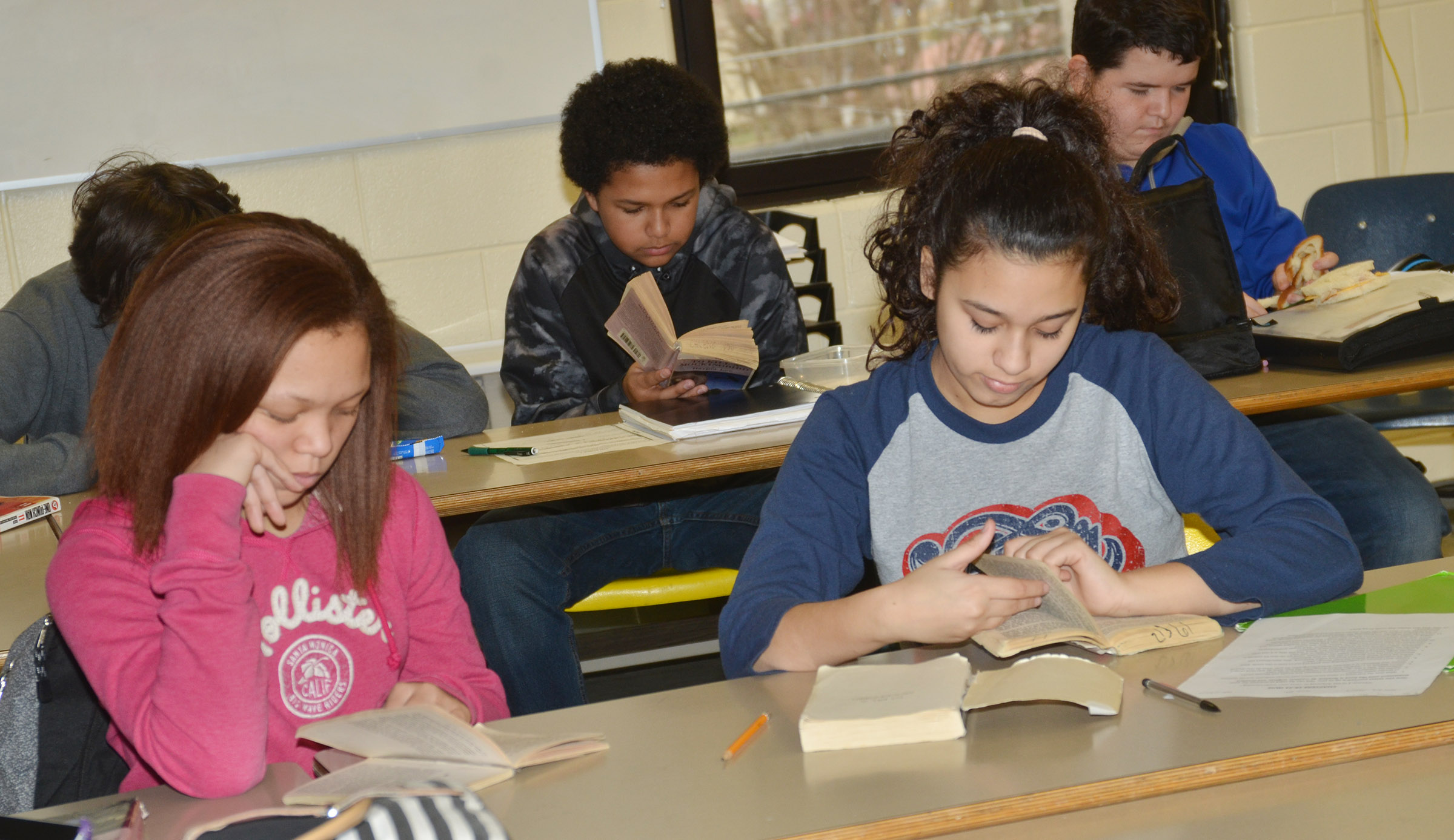"Campbellsville Middle School eighth-graders Kitana Taylor, at left, and Bia Moura follow along as teacher Tyler Hardy reads ""To Kill A Mockingbird."""