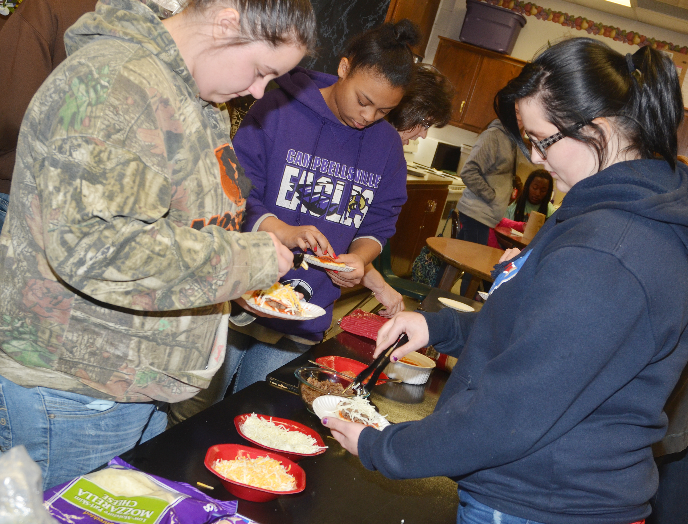 From left, CHS sophomore Amanda Dotson, freshman Alexis Lane and senior Cassie Pendleton make English muffin pizzas.
