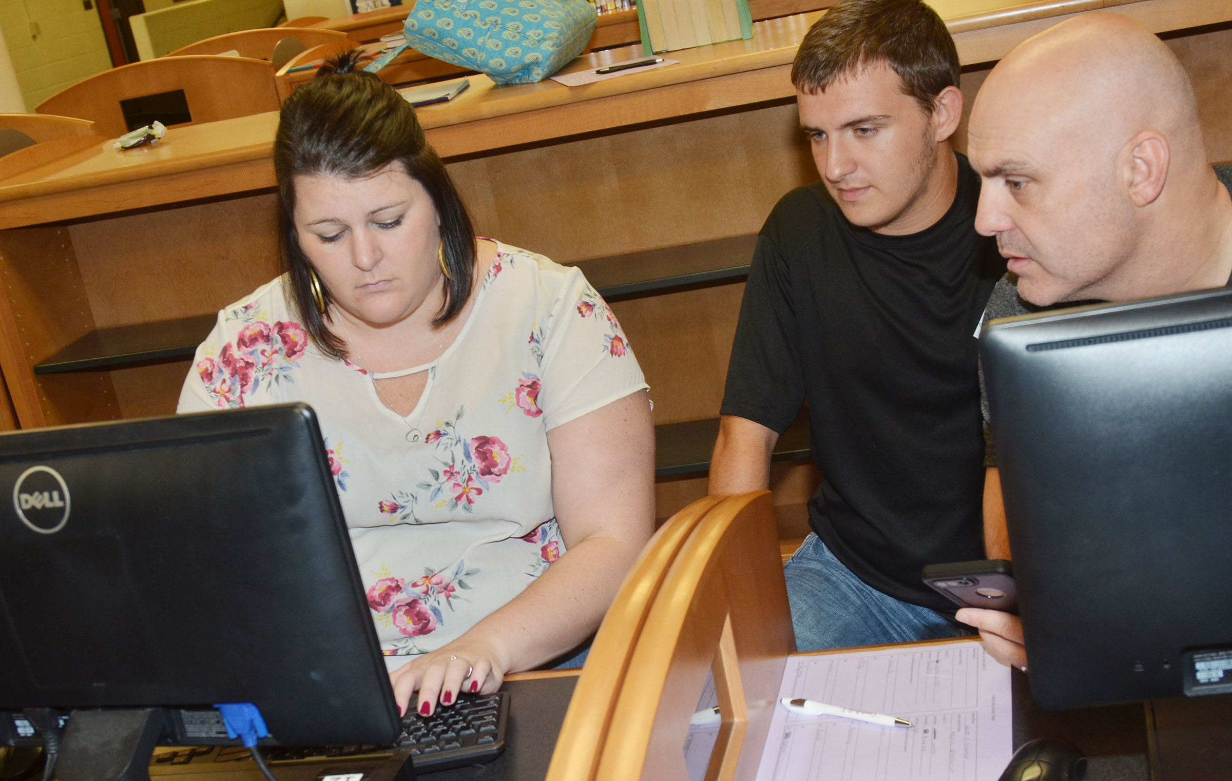 Kentucky Higher Education Assistance Authority representative Audrey Price helps CHS senior Austin Fitzgerald complete his FAFSA with his father Andy.