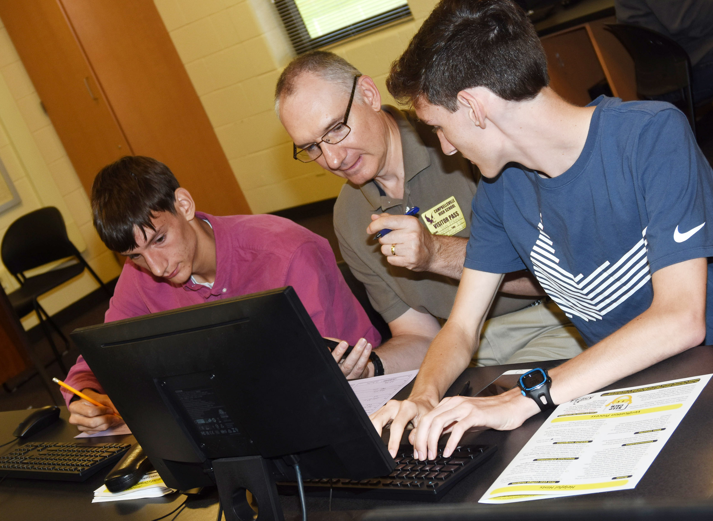 CHS seniors Evan McAninch, at left, and Ian McAninch complete the FAFSA with their father, Troy.