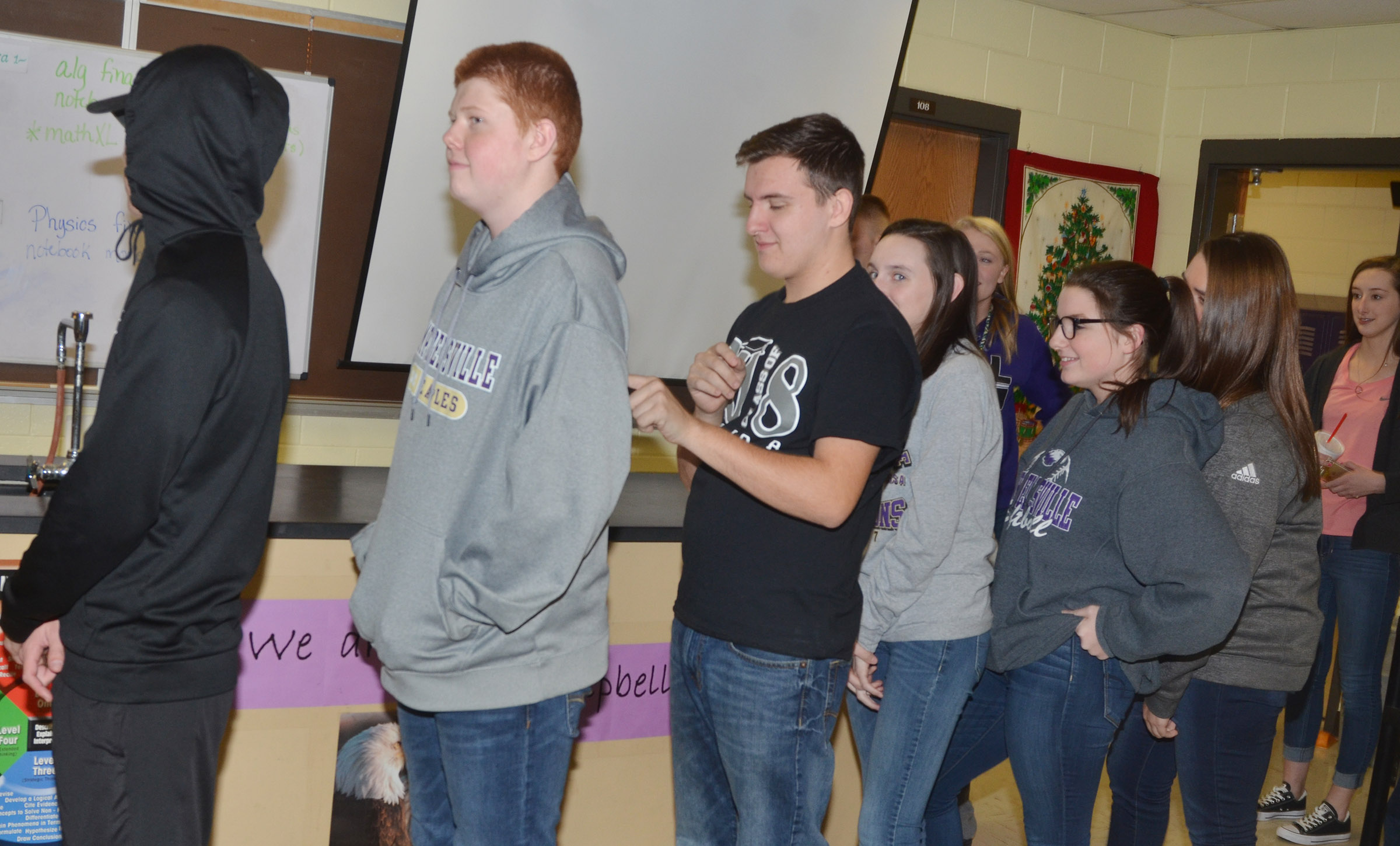 "CHS FCA members play an icebreaker game in which students form a line and ""write"" a symbol on each other's backs. The person at the front of the line tries to guess the symbol. Above, CHS senior Austin Fitzgerald ""writes"" on freshman Colin Harris's back."