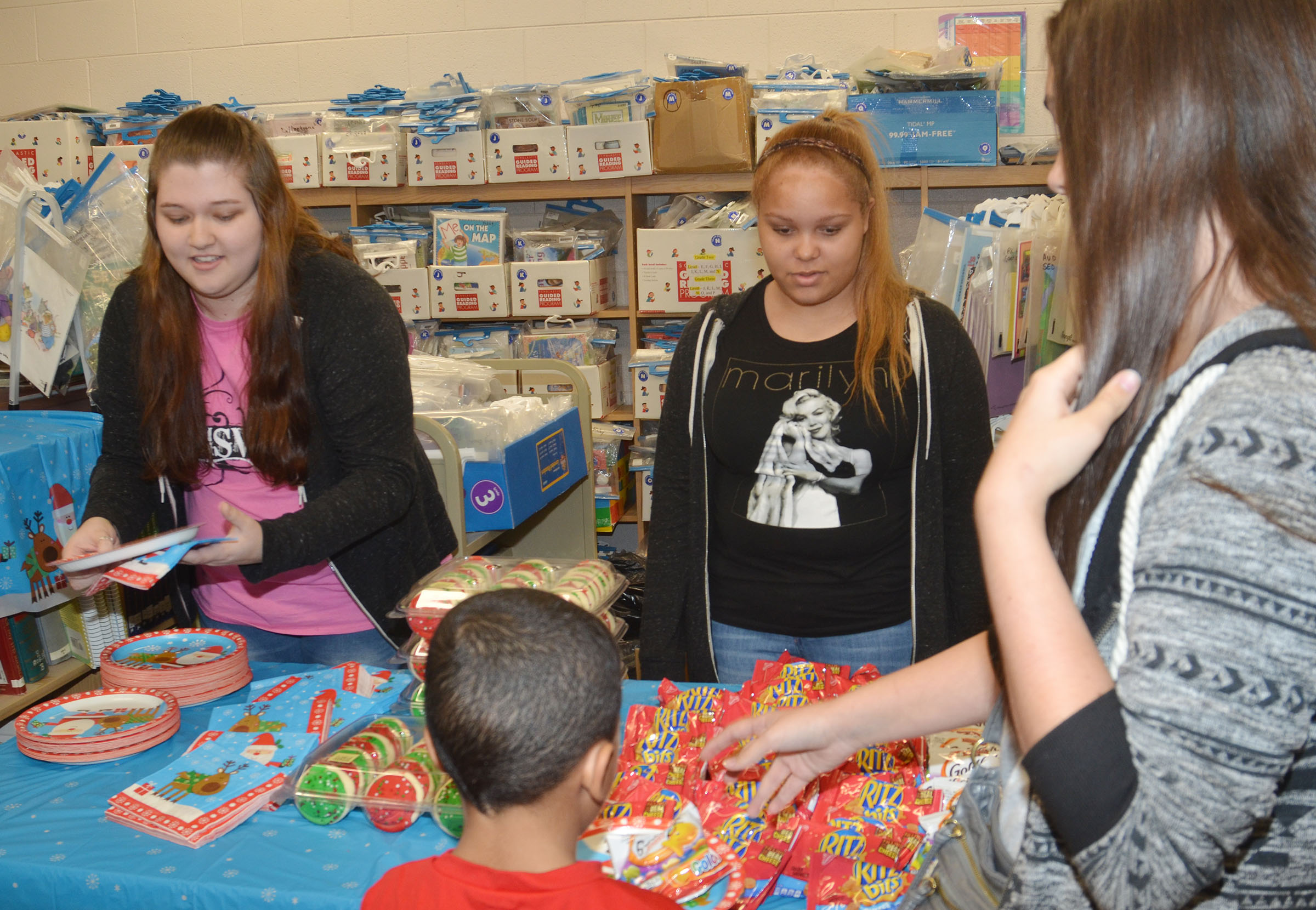 CHS FCCLA members, from left, juniors Lauren Riddle, Shailyn Fields and Makala Antle serve snacks at a Christmas party for Campbellsville Elementary School students.
