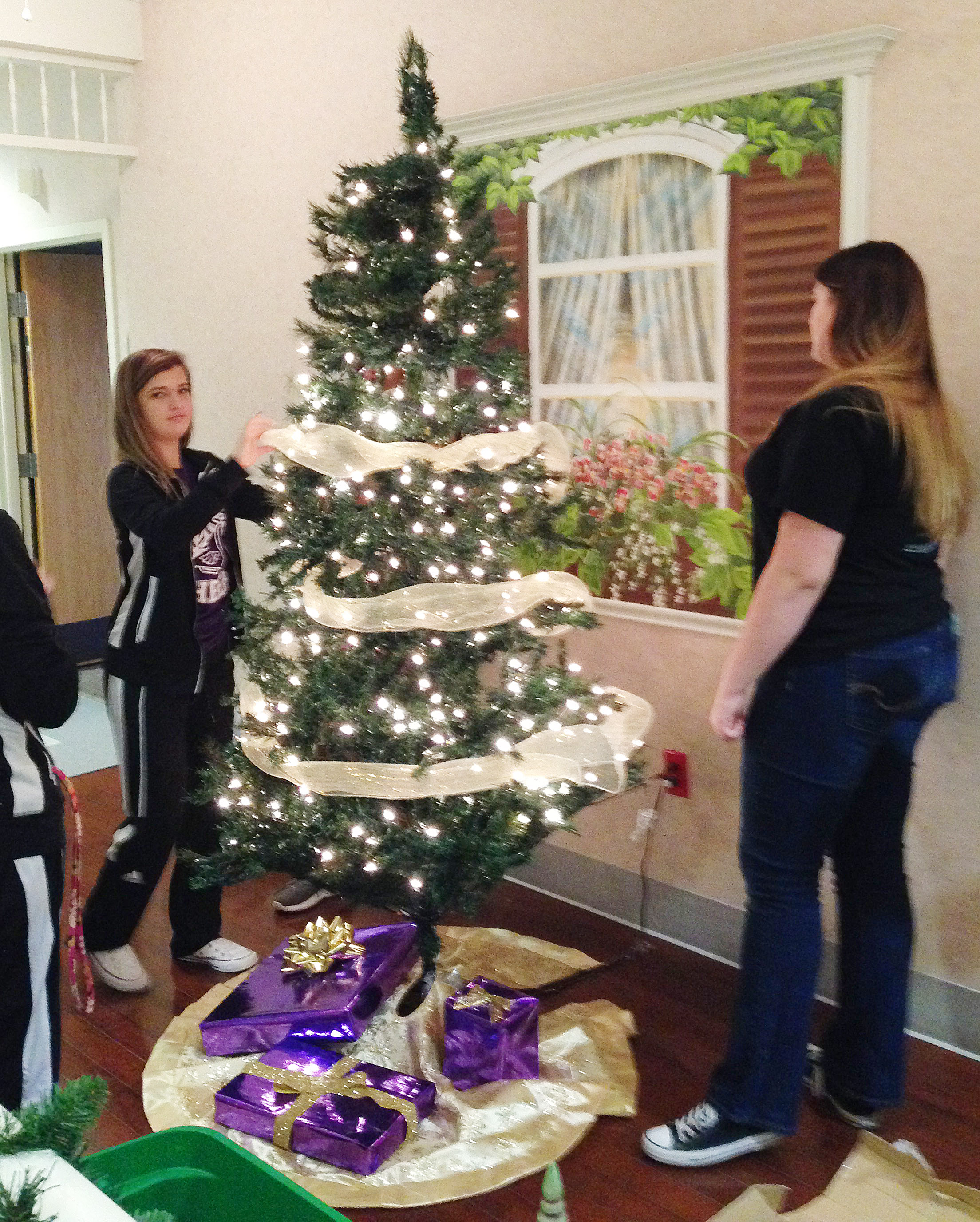 CHS freshman Carly Adams, at left, and senior Vivian Brown decorate the FCCLA club's Christmas tree, which is on display at the Grandview.
