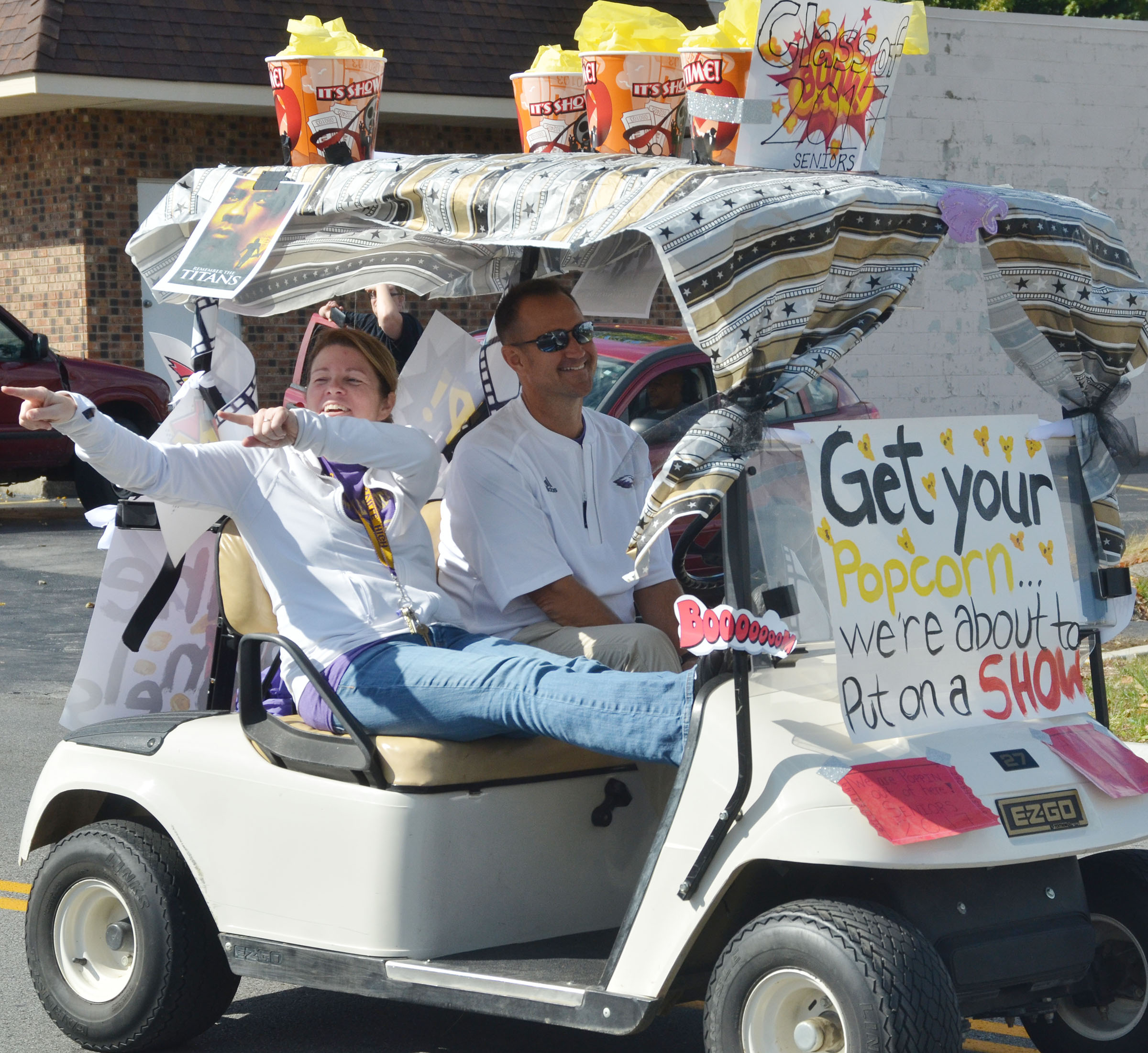CHS teachers Dee Doss, at left, and Steve Doss drive the senior golf cart in the homecoming parade.