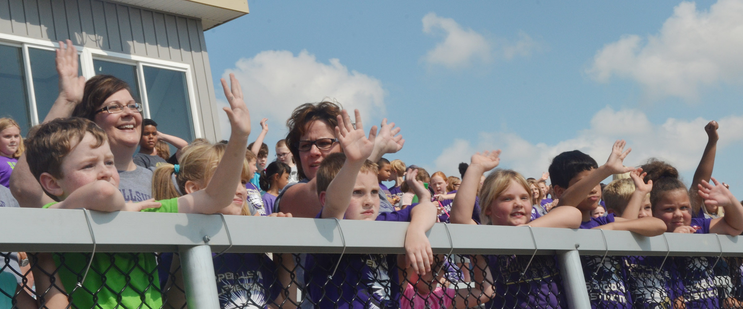 CES second-graders wave to those riding in the parade.