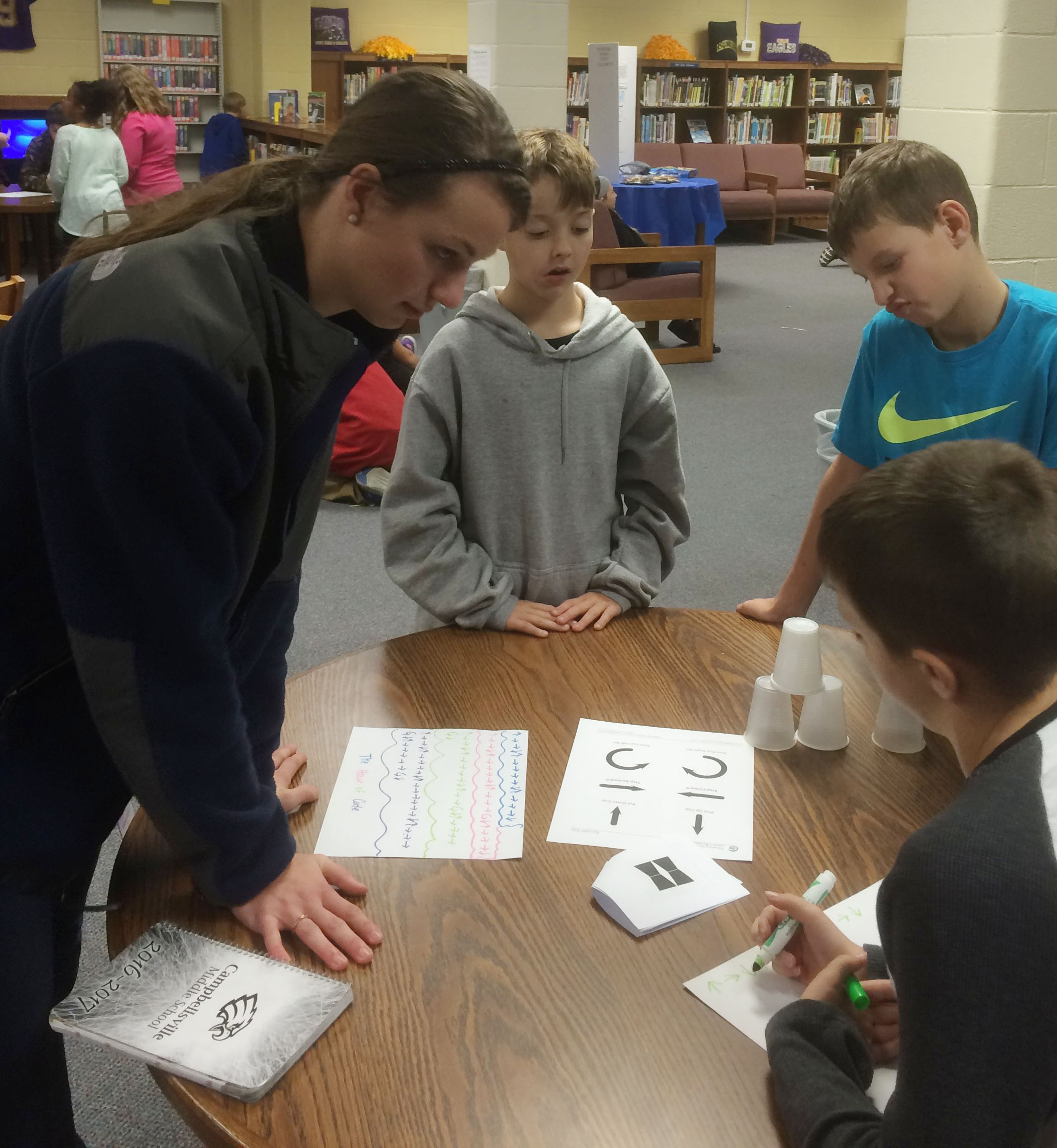 CHS senior Caylie Blair teaches CMS fourth-graders about computer coding.