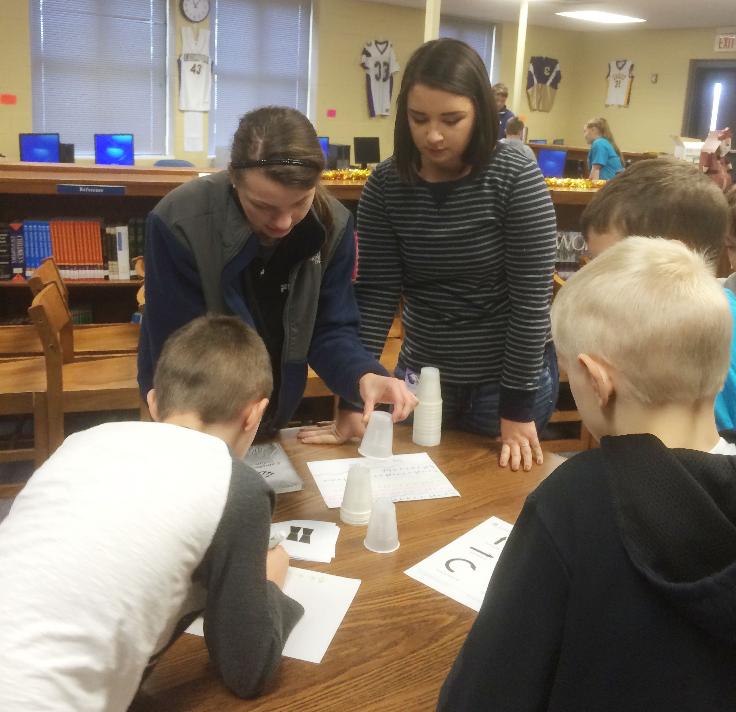 CHS seniors Caylie Blair, at left, and Kailey Morris teach CMS fourth-graders about computer coding.