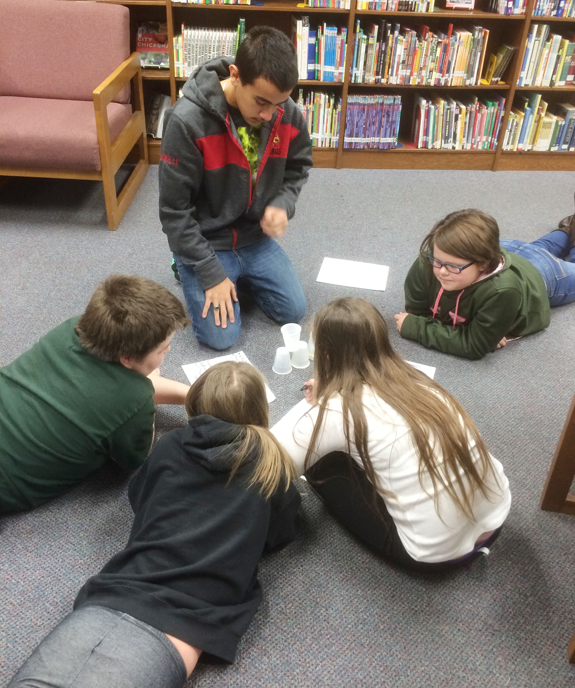 CHS sophomore Glenn Lamer teaches CMS fourth-graders about computer coding.
