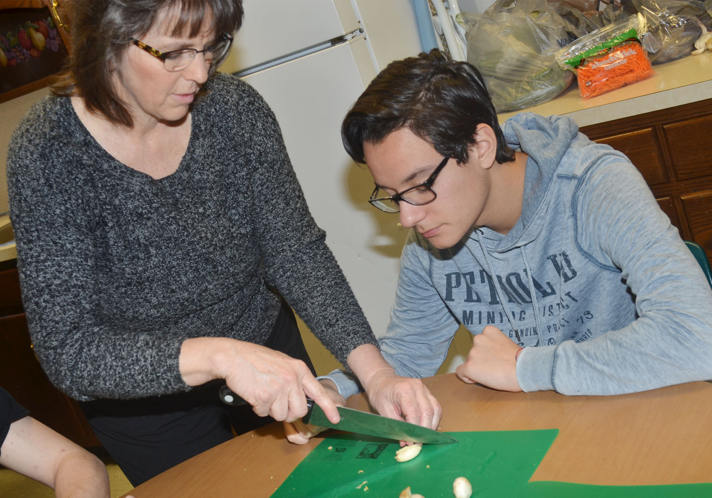 CHS foods and nutrition teacher Deanna Campbell helps junior Matteo Rossi chop garlic.