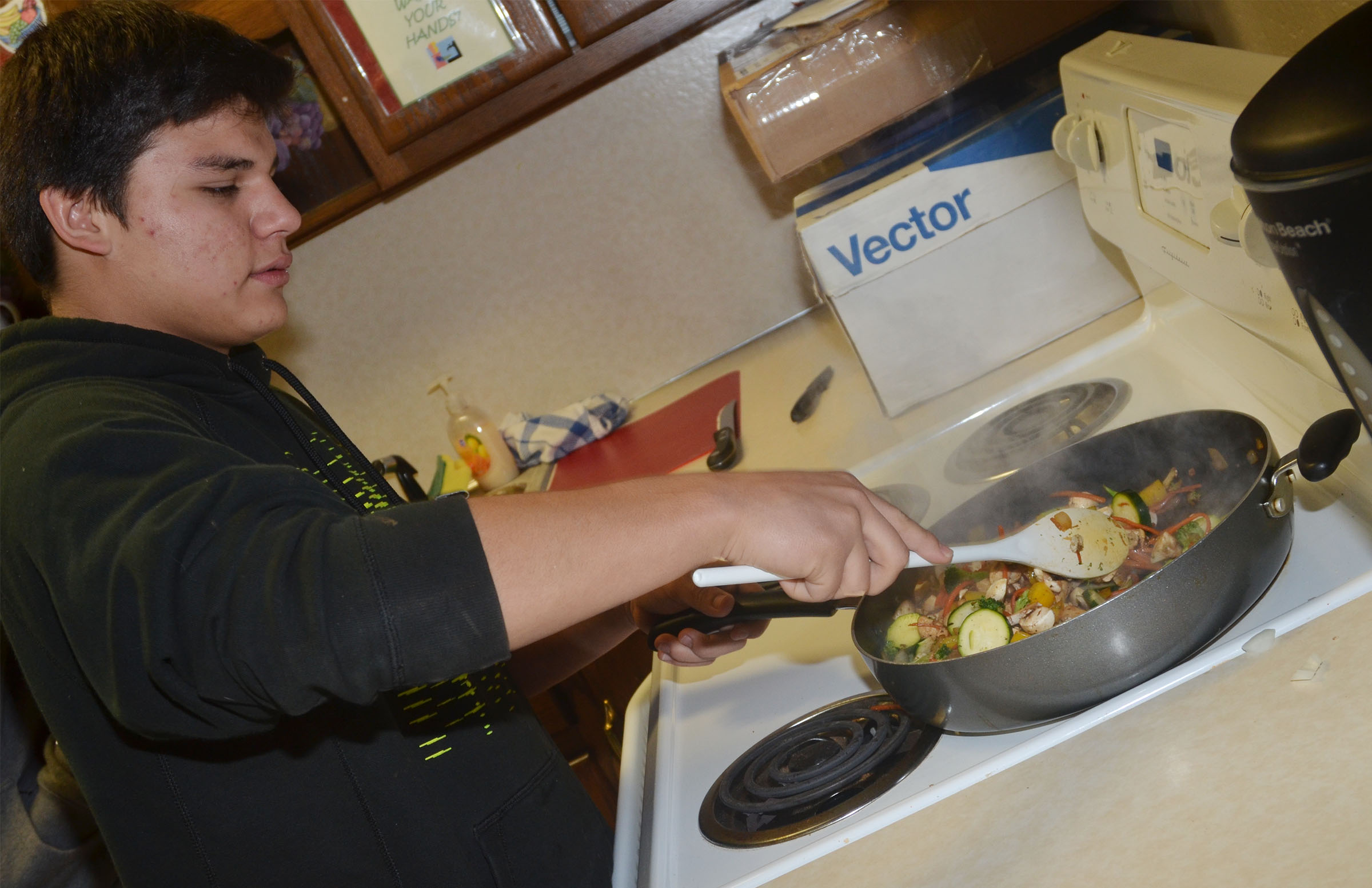 CHS freshman Greg Lopez mixes the stir fry.