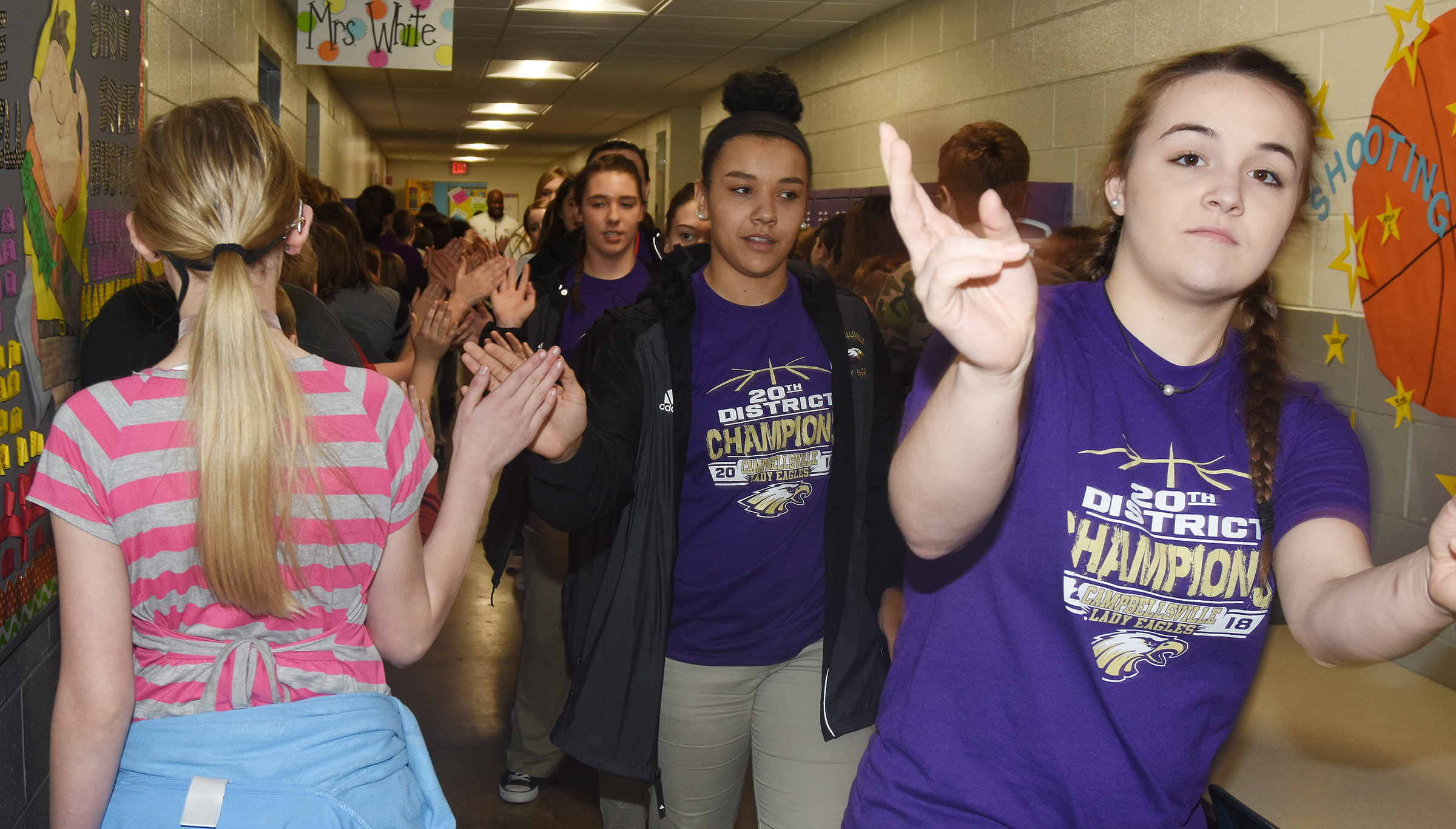 CHS girls' basketball player Vonnea Smith, a freshman, and her teammates high-five CES students.