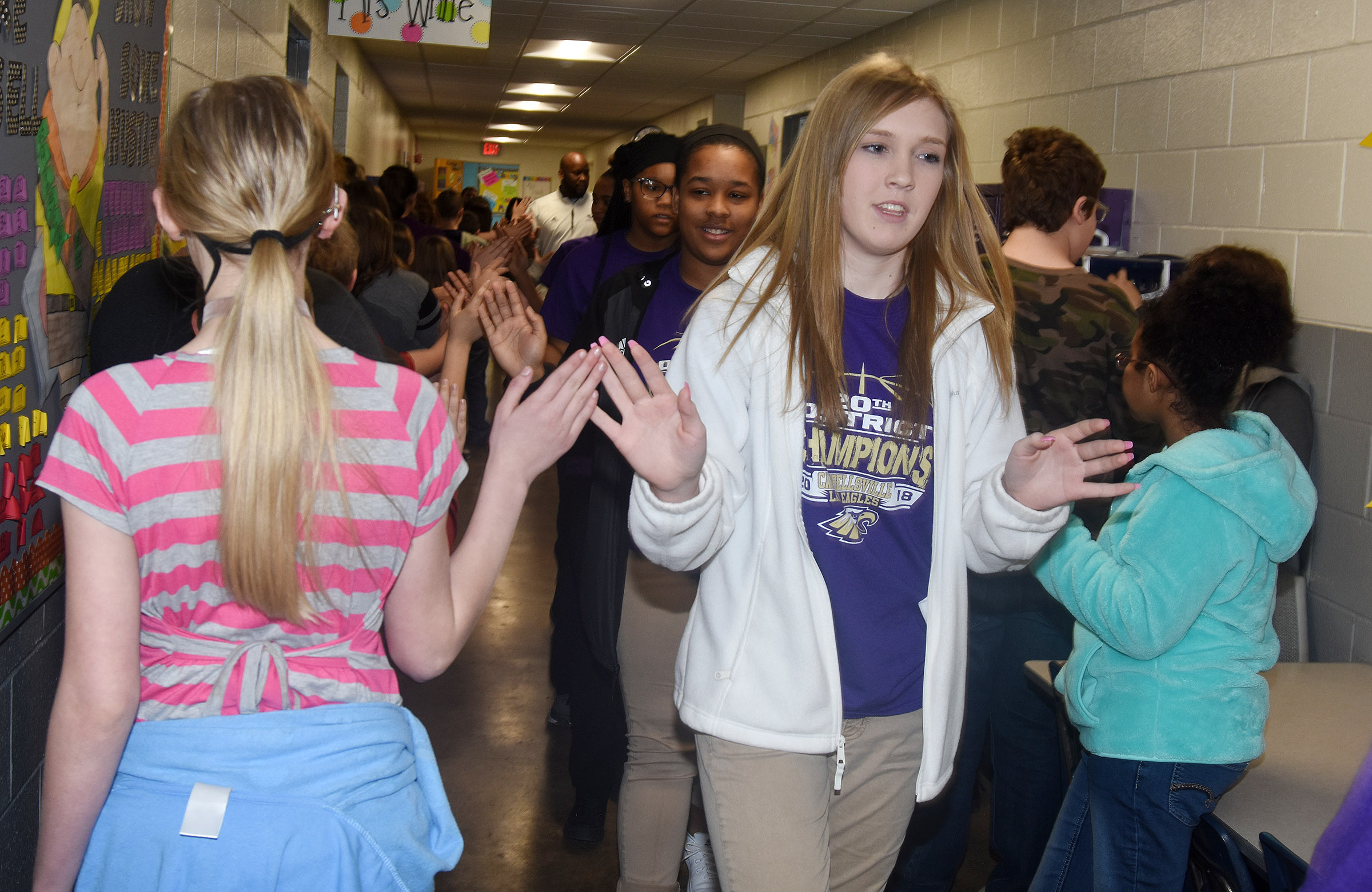 CHS girls' basketball player Catlyn Clausen, a freshman, and her teammates high-five CES students.