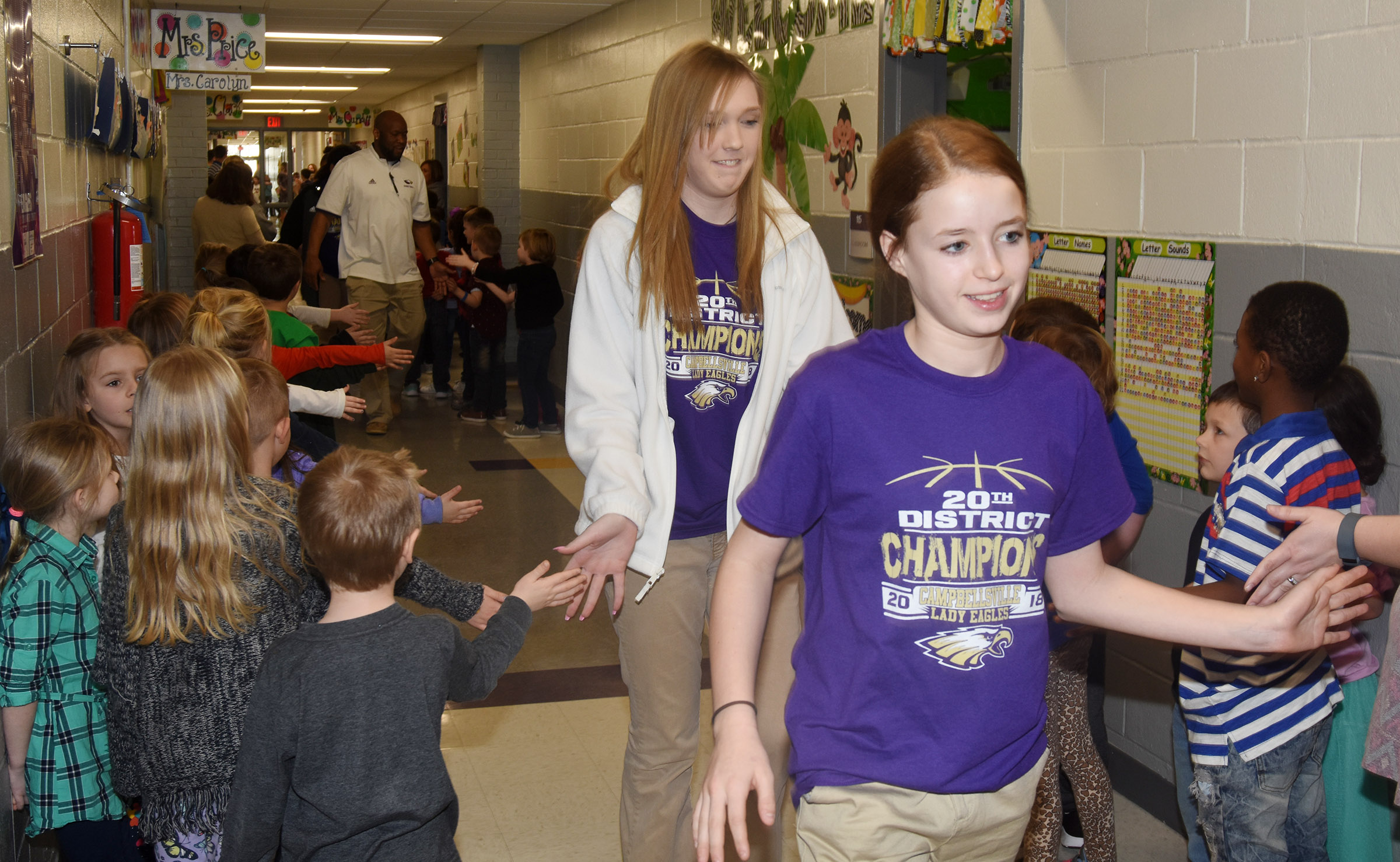 CHS girls' basketball players Catlyn Clausen, at left, a freshman, and Campbellsville Middle School eighth-grader Rylee Petett high-five CES students.