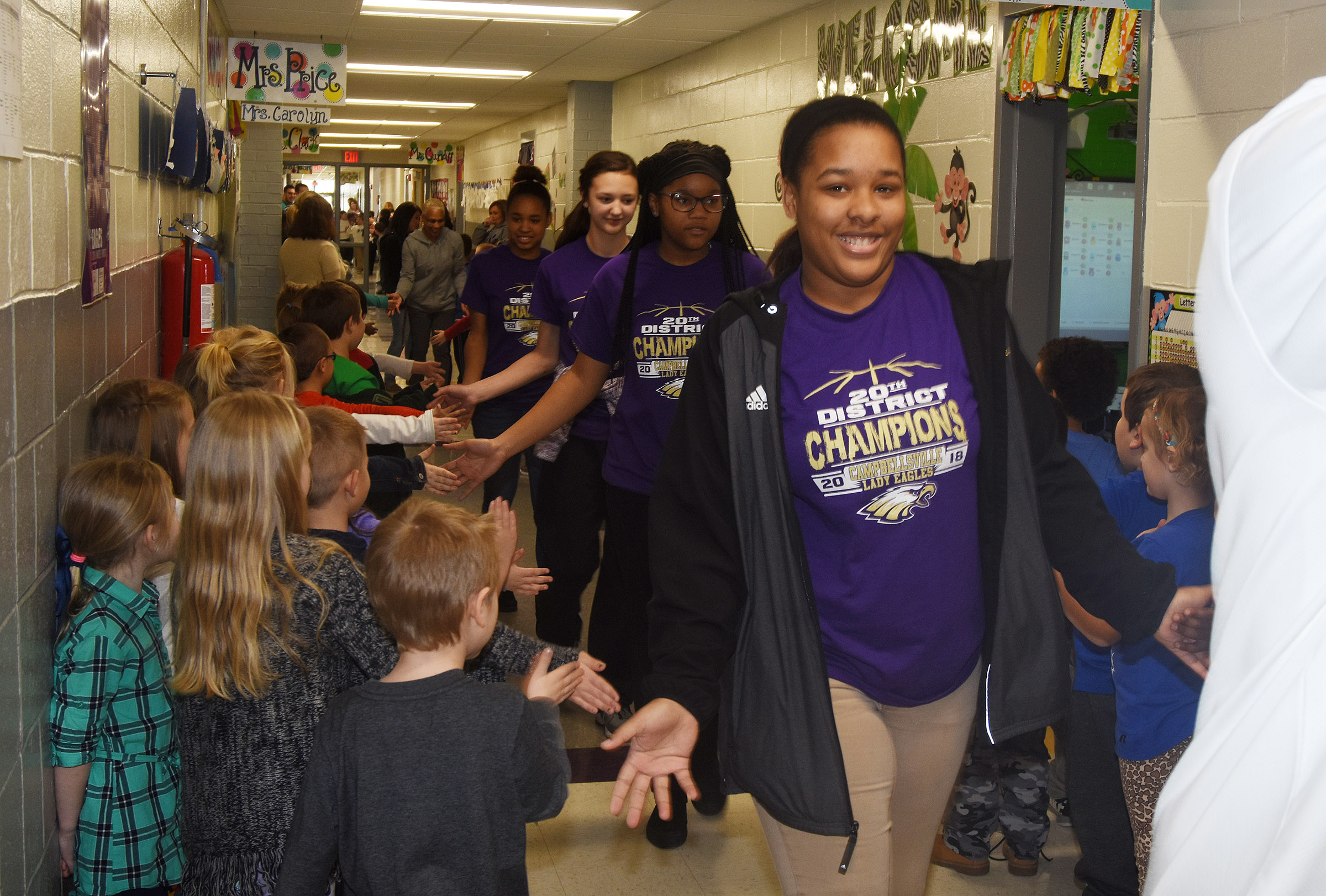 CHS girls' basketball player Kayla Young, a senior, and her teammates high-five CES students.