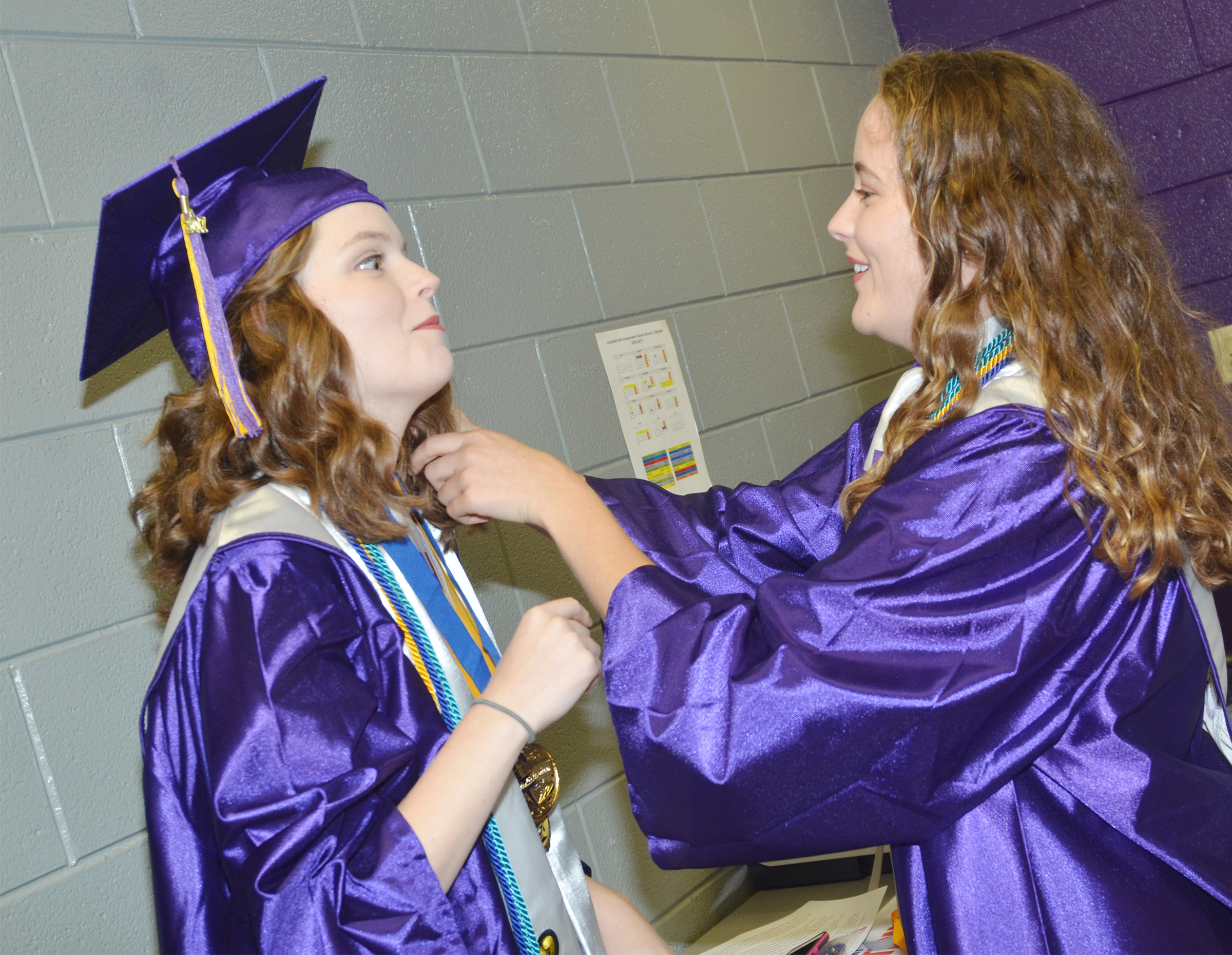 CHS senior Caroline McMahan, at right, helps classmate Blair Lamb straighten her honor cords before graduation.