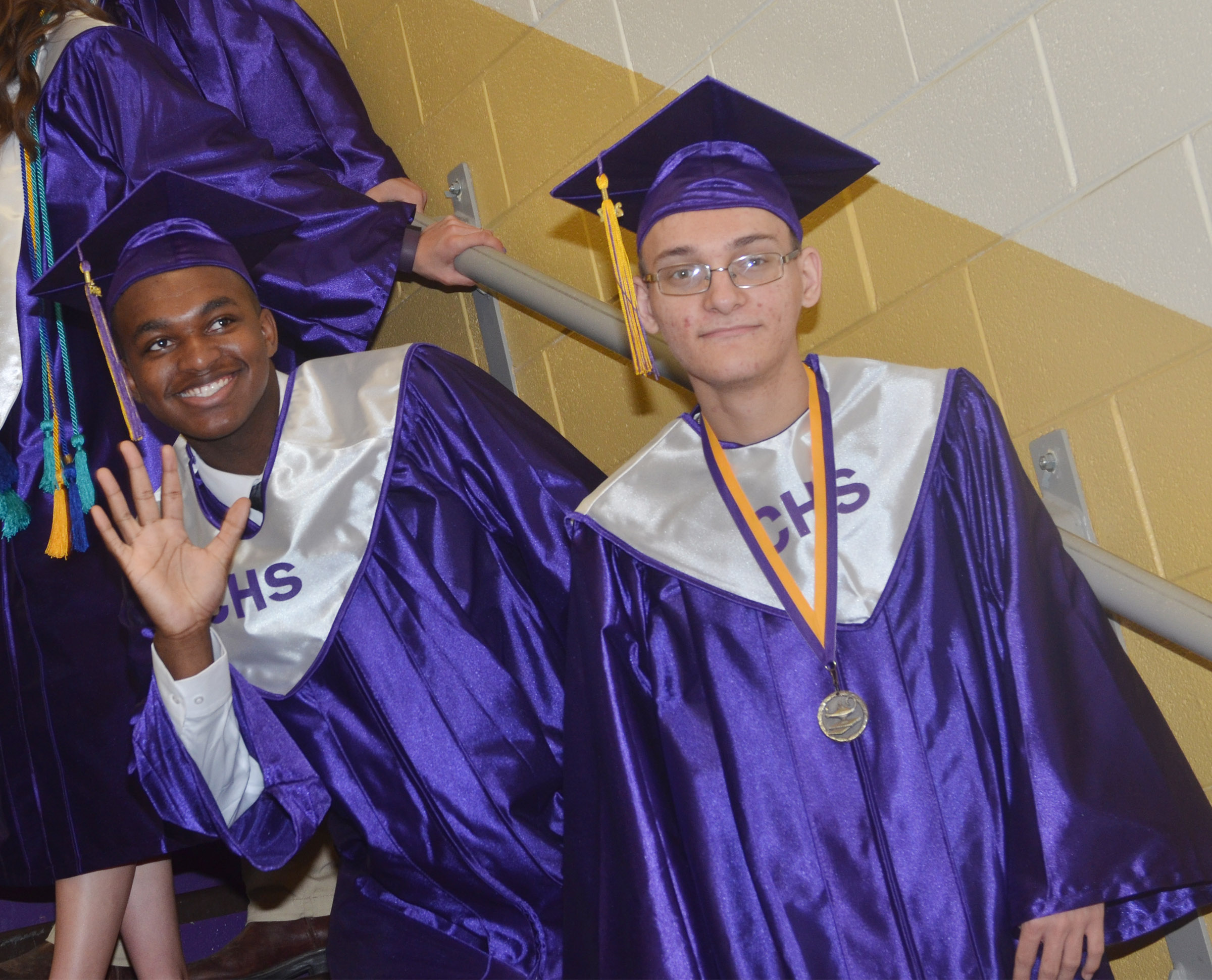 CHS senior Darius Bell, at left, waives to his family as he and classmate Chase Atwood wait for the graduation ceremony to begin.