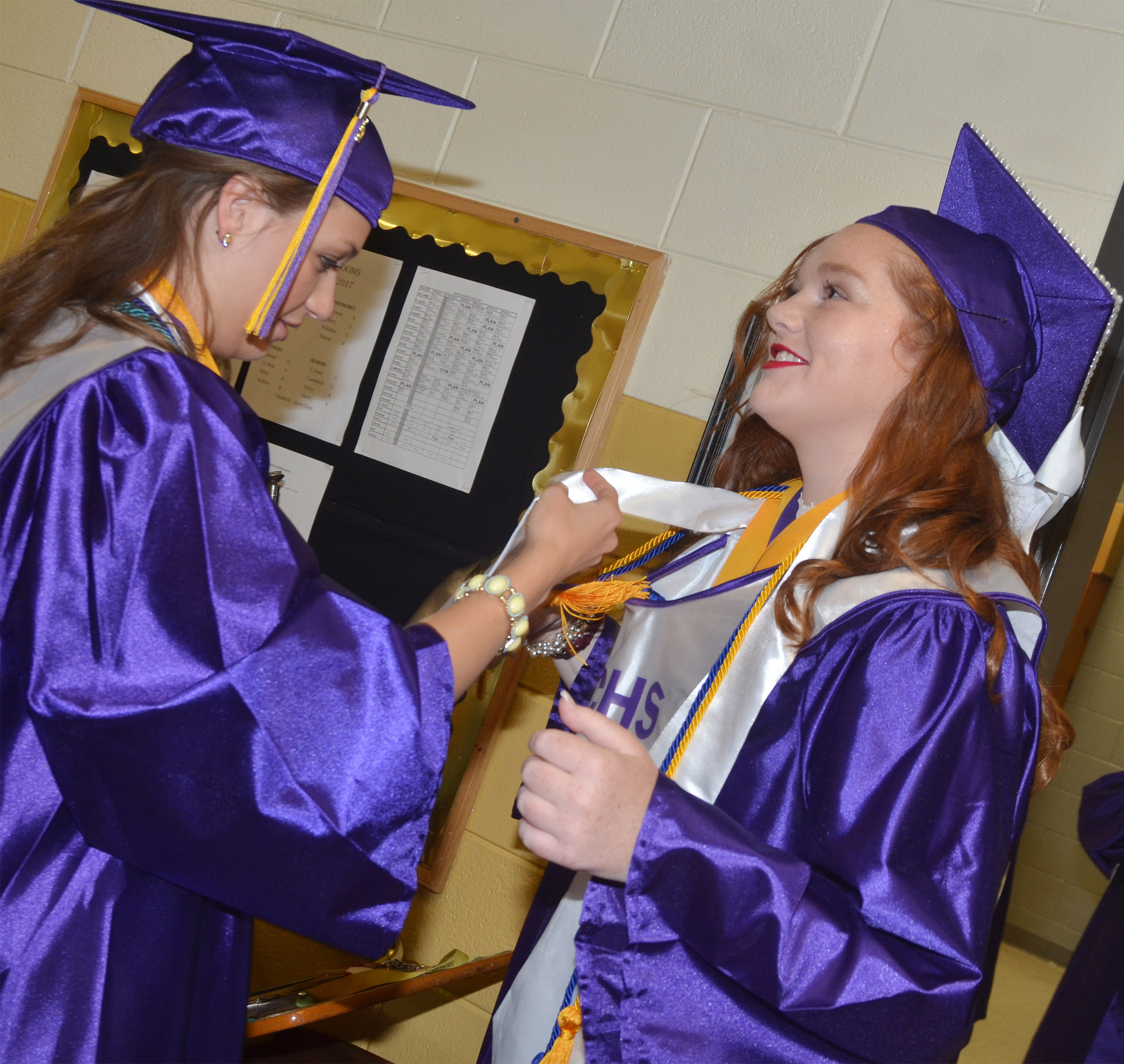 CHS senior Caylie Blair helps classmate Mallory Haley with her honor cords before graduation.