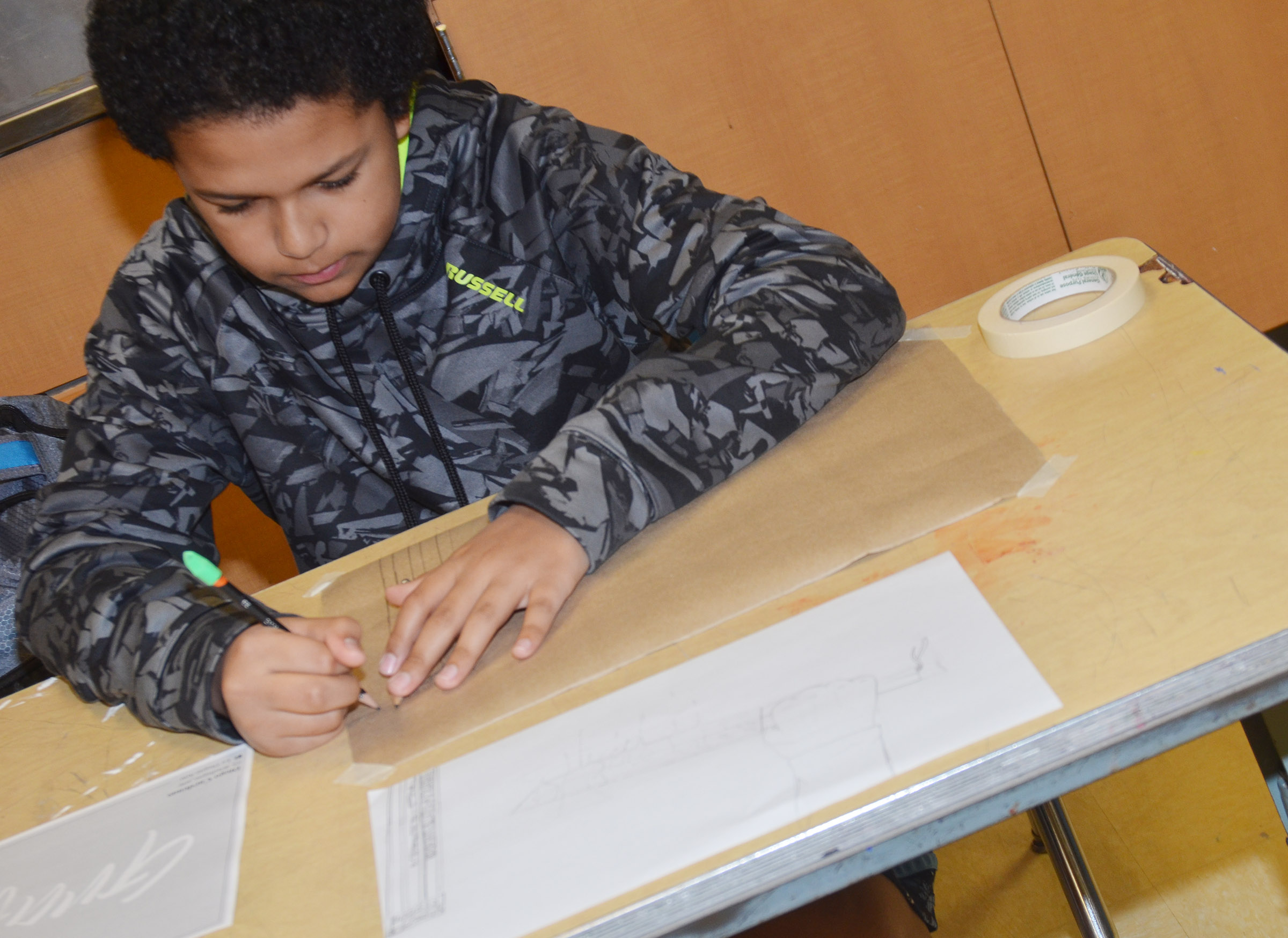 Campbellsville Middle School eighth-grader Tezon Mitchell draws his graffiti-style art.