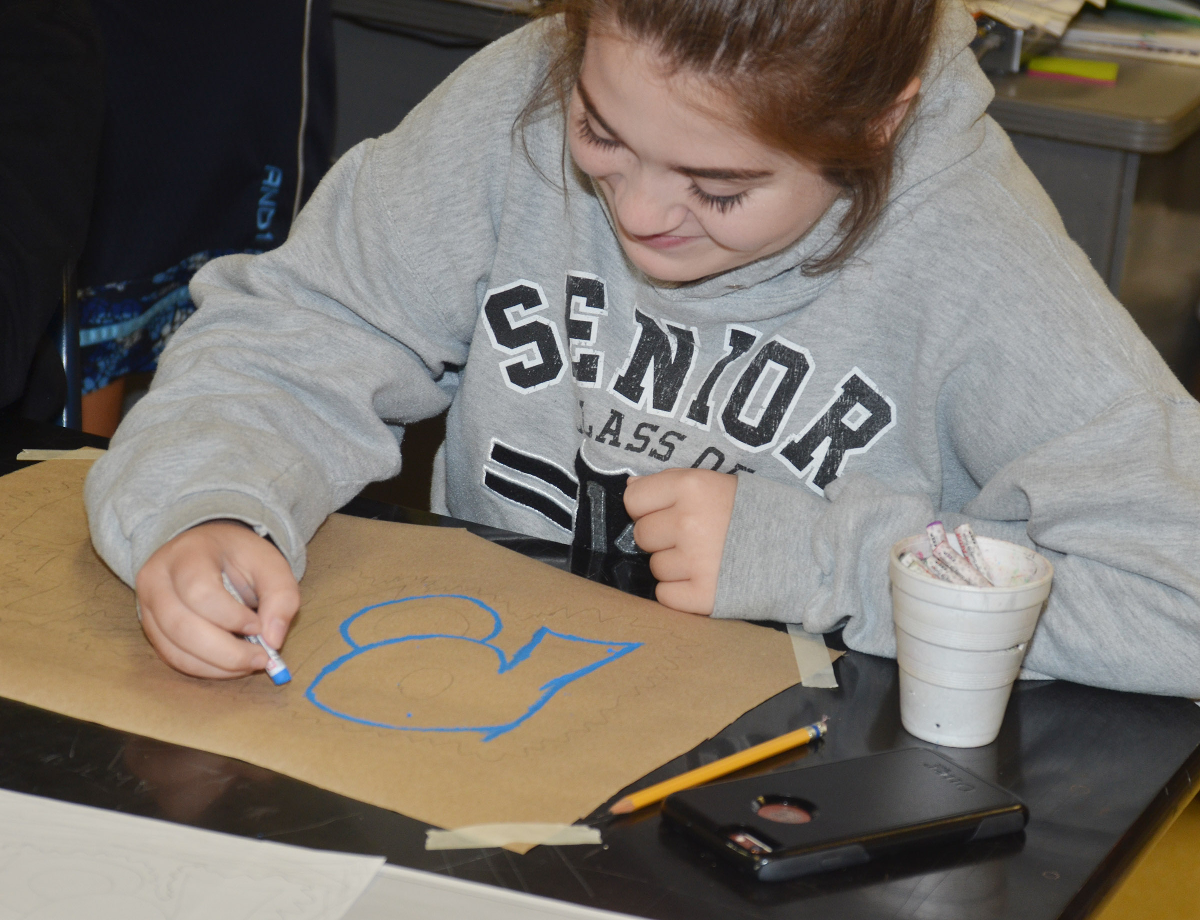 CHS freshman Chloe Garrett uses oil pastels to add color to her graffiti-style art.