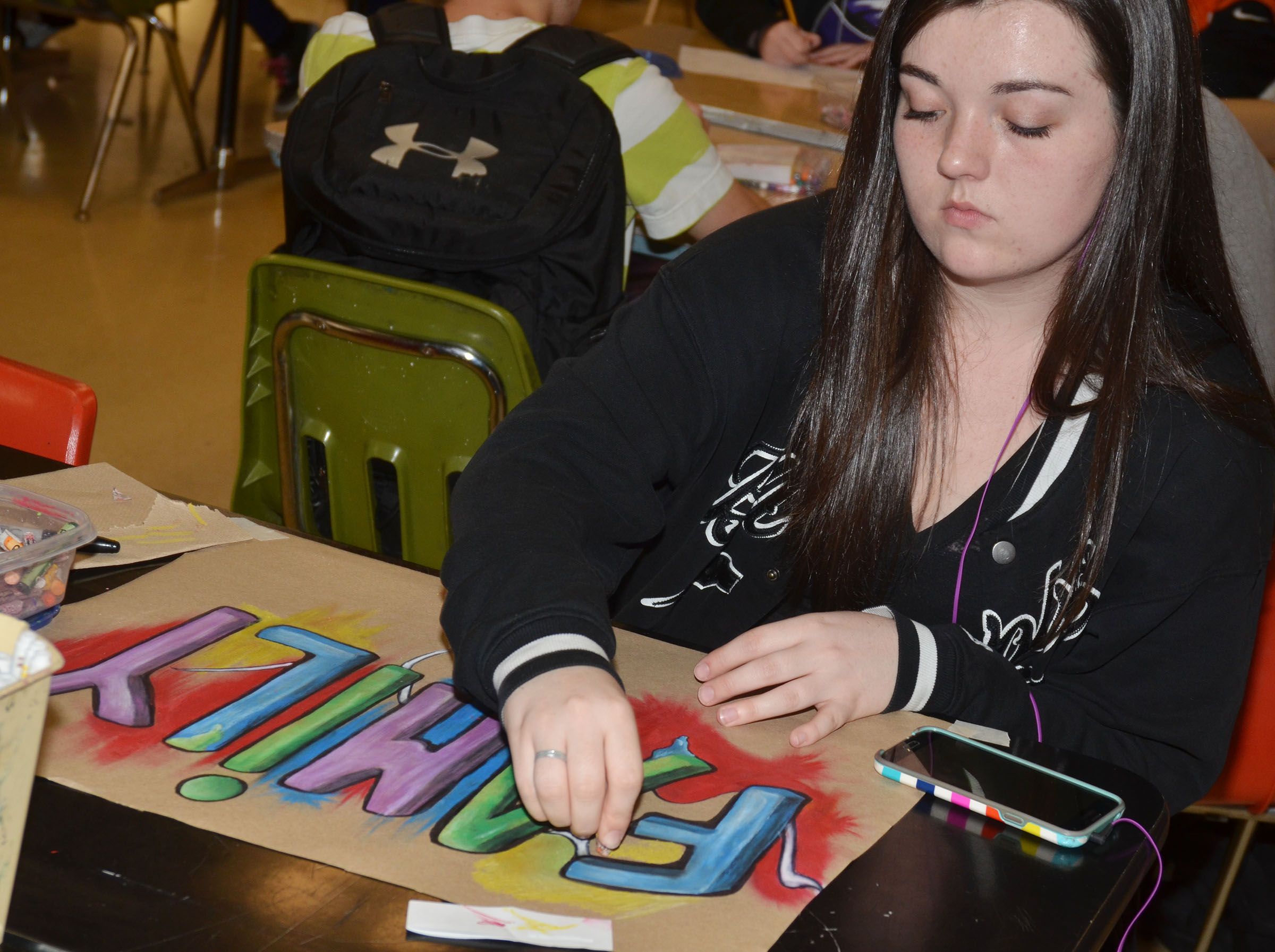 CHS senior Tiffany Stagner puts finishing touches on her graffiti-style art.