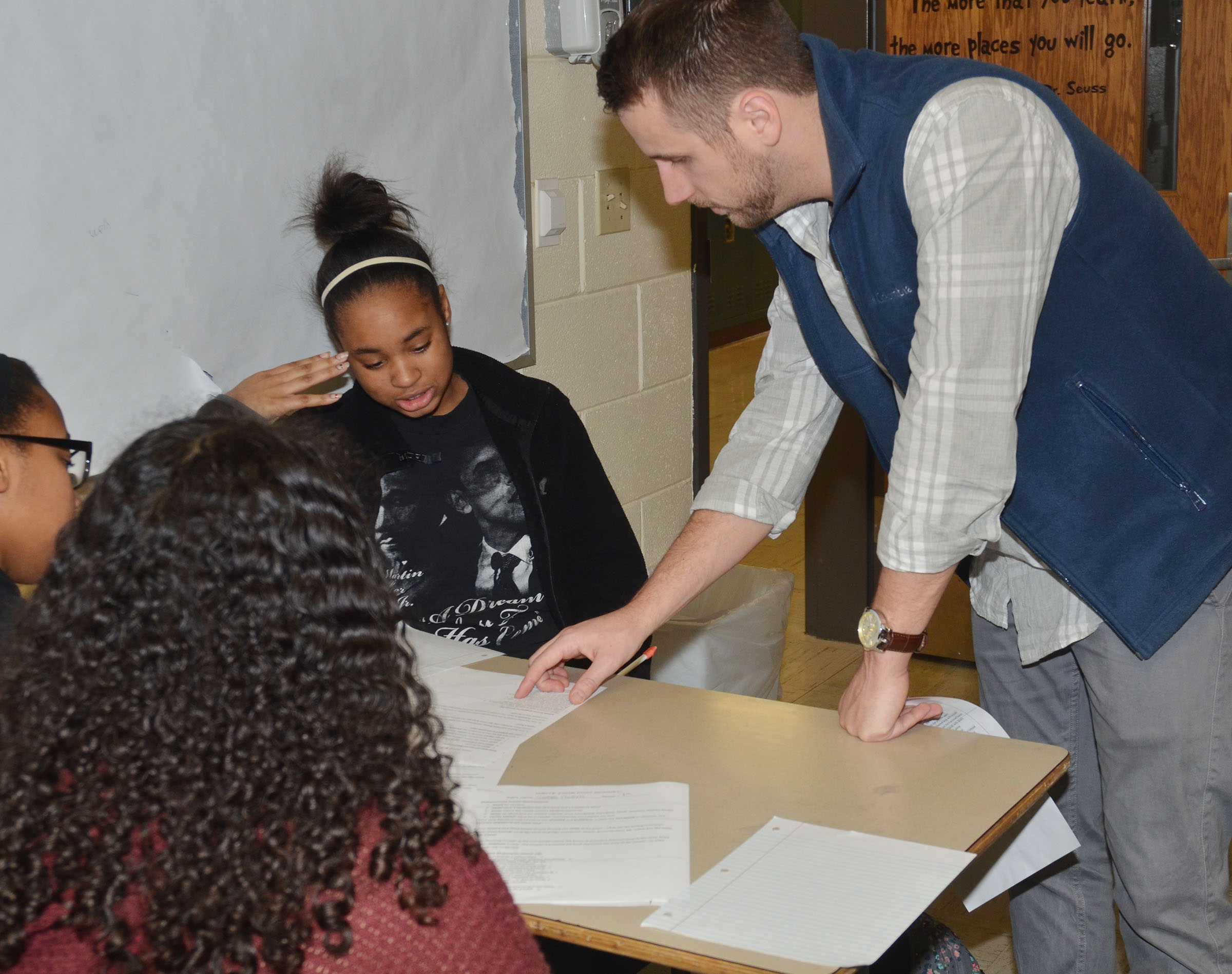 CHS English teacher Tyler Hardy talks to freshman Isis Coleman and her classmate about her sonnet.