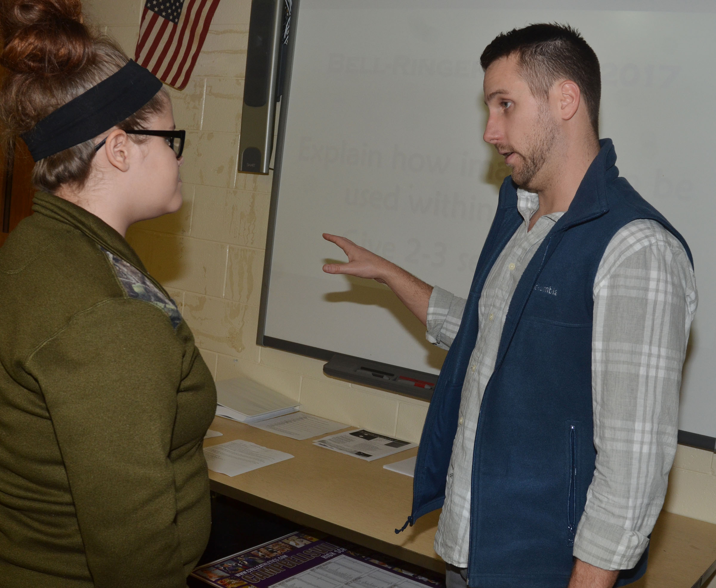 CHS English teacher Tyler Hardy talks to freshman Caylee Shofner about her sonnet.