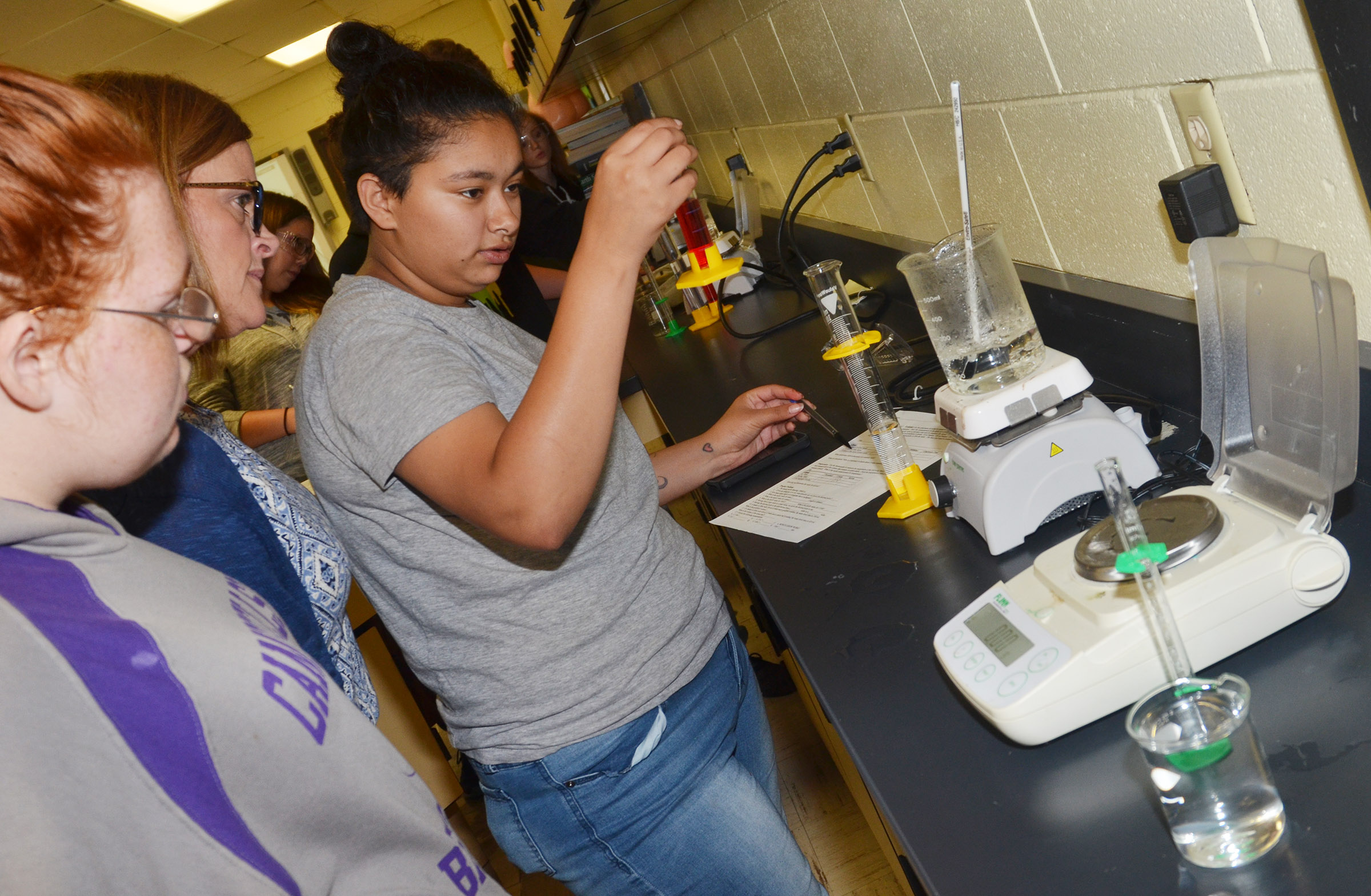 CHS sophomore Cristina Barrera measures water as freshman Jadelyn Caffee and teacher Mary Jo Hazel watch.