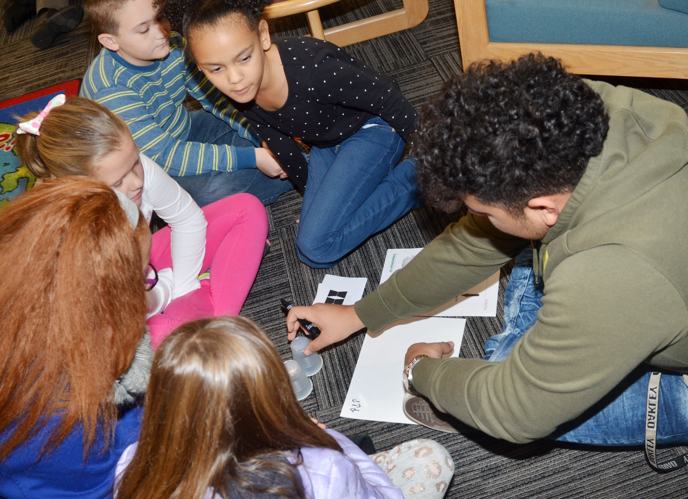 CHS senior Adrian Cravens teaches CES third-graders how to write computer coding.