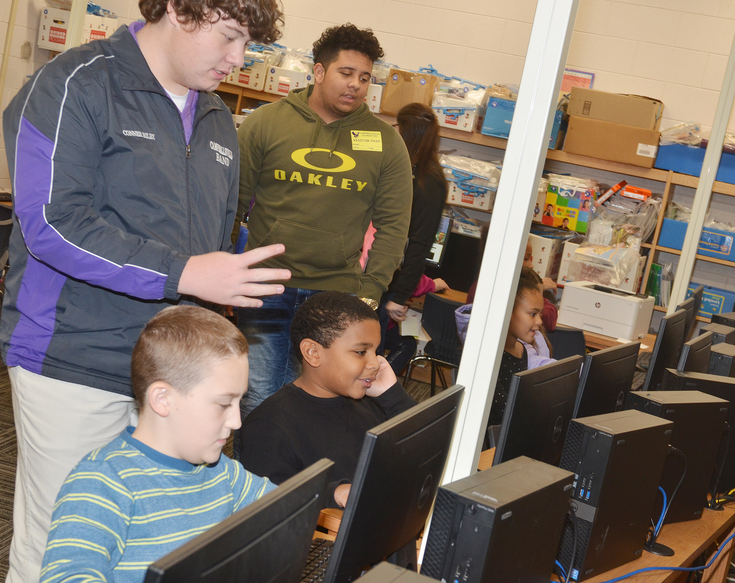 CHS sophomore Conner Riley, at left, and senior Adrian Cravens teach CES third-graders how to use a computer game to write coding.