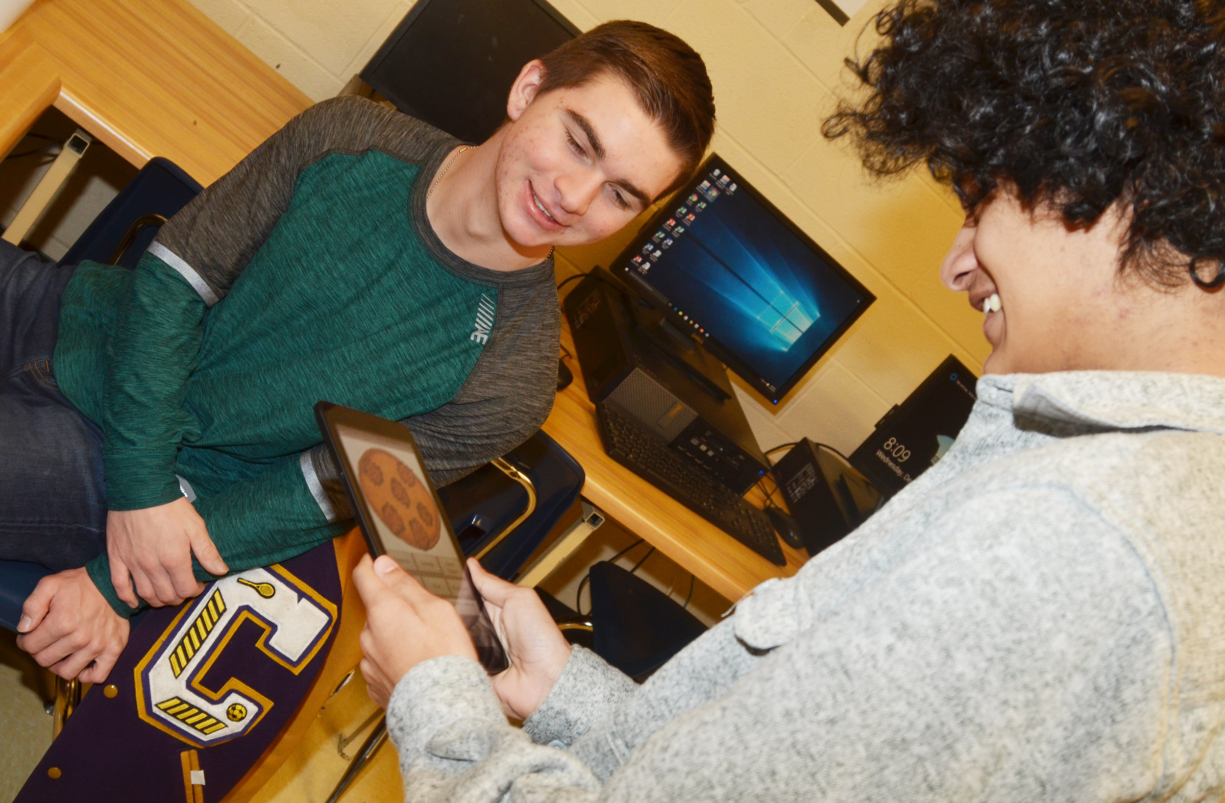 "CHS senior Cass Kidwell lets sophomore Ben Arachi use his app to ""order"" a pizza."