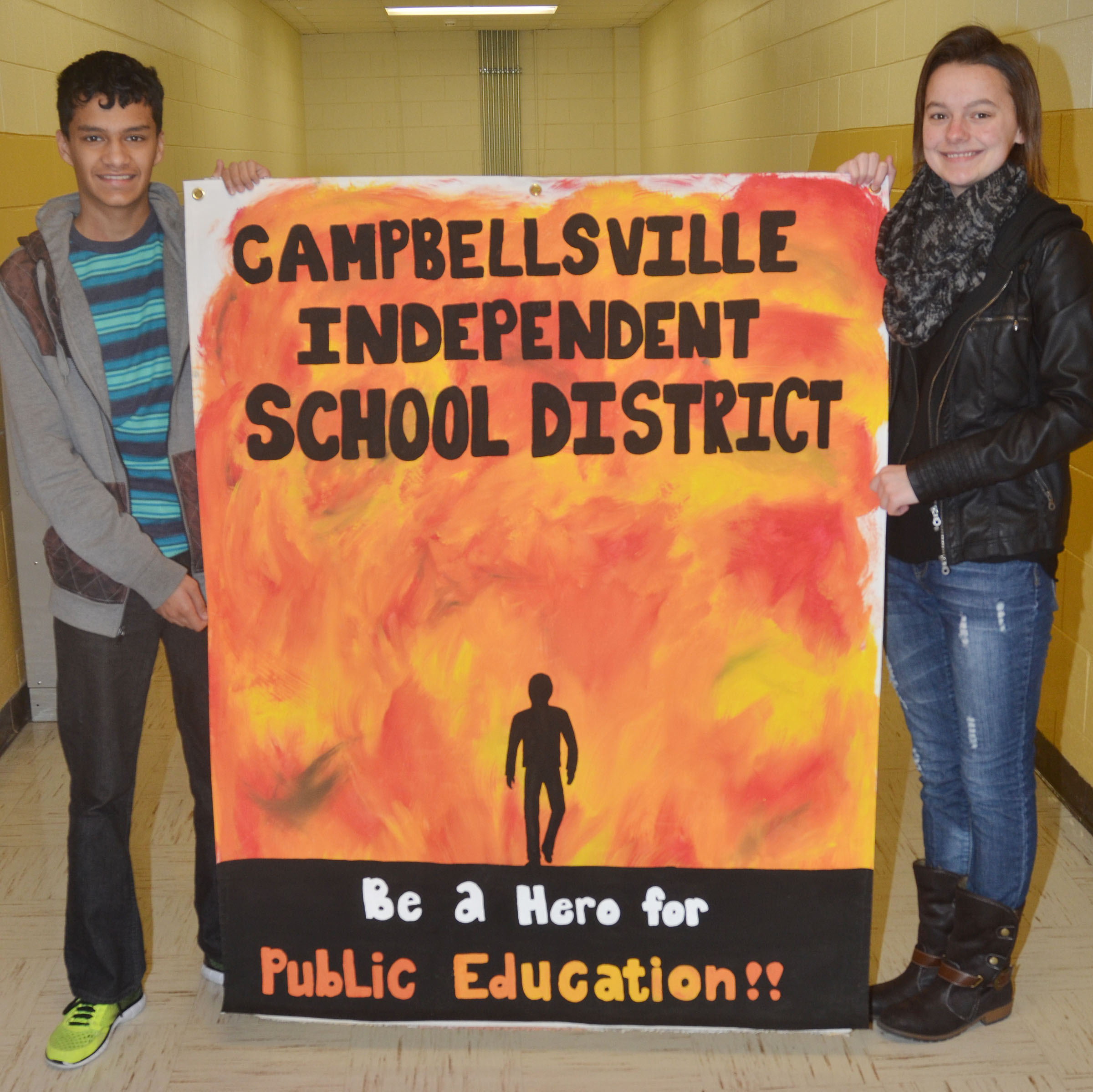 "CHS National Art Honor Society member Kyrsten Hill, at right, a senior, made this banner for display at the KSBA annual conference, with the theme ""Be a superhero for Public Education."" Ben Arachi, a freshman, created the design for the poster."