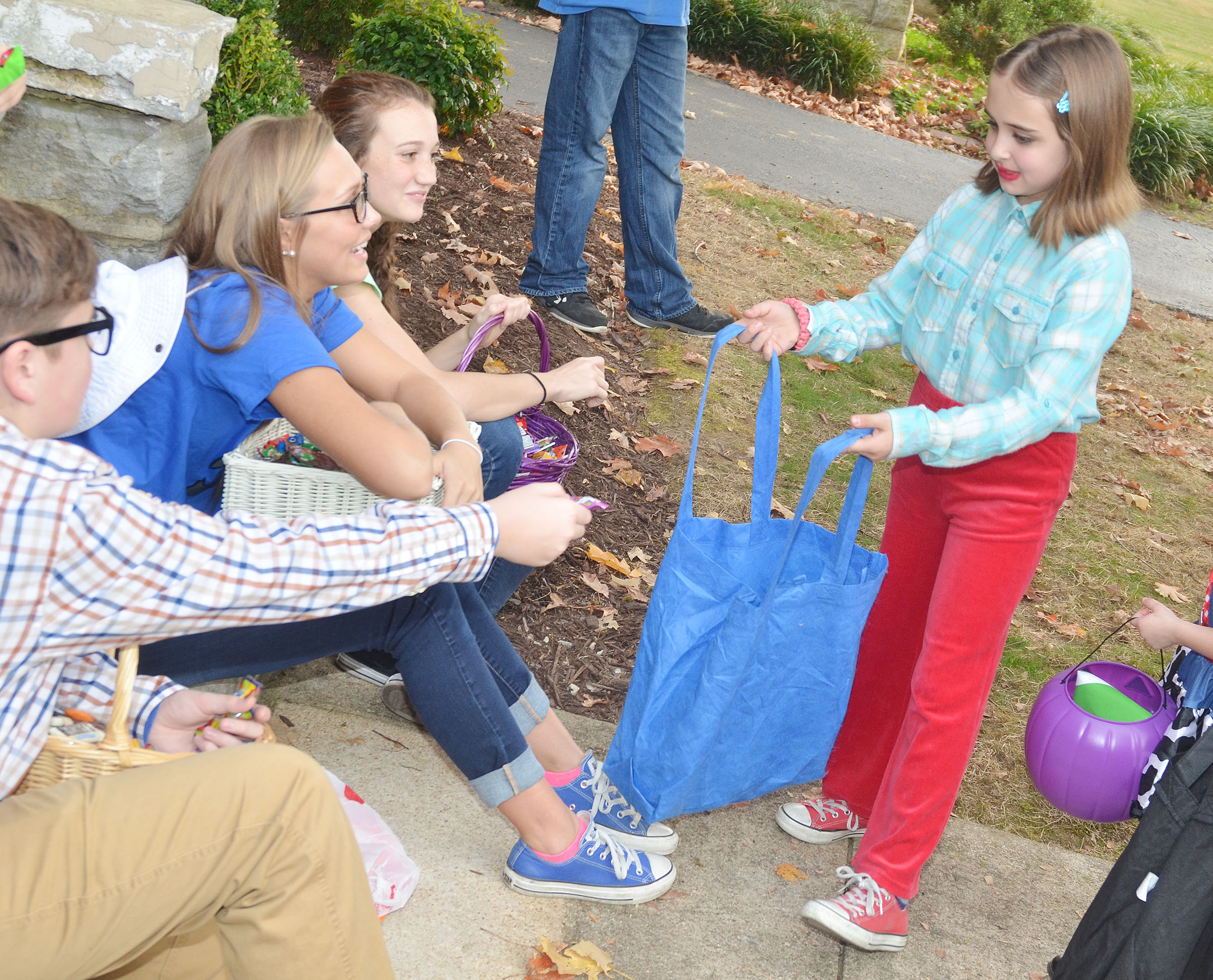 CHS KYA members, from left, freshman Gavin Johnson and sophomores Tatem Wiseman and Salena Ritchie pass out Halloween candy to Campbellsville Middle School fourth-grader Anna Floyd.