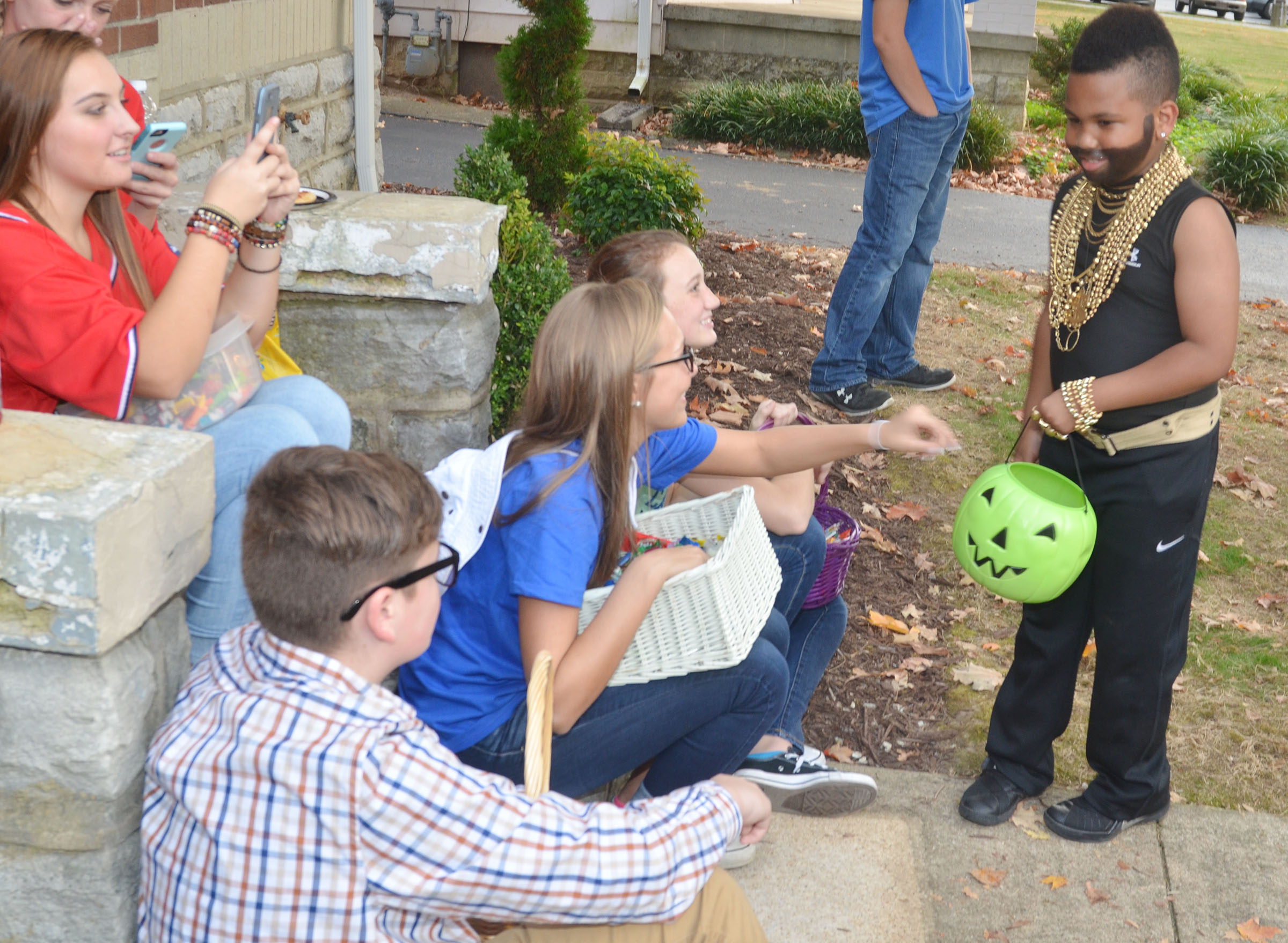 CHS KYA members, from left, freshman Gavin Johnson and sophomores Tatem Wiseman and Salena Ritchie pass out Halloween candy to Campbellsville Middle School fifth-grader Devin Kinser, as sophomore Reagan Knight takes a photo of his Mr. T costume.