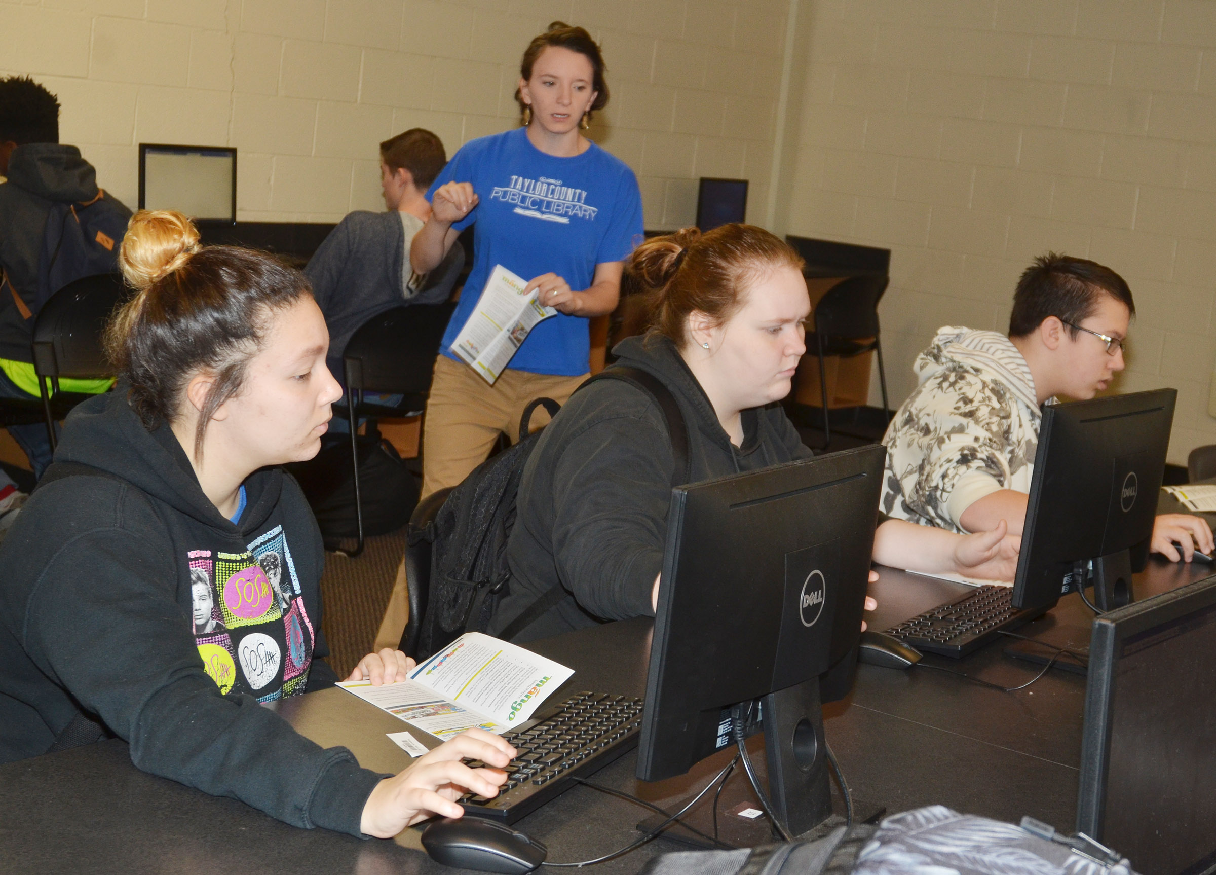 Kelsie Pepper of Taylor County Public Library helps CHS freshmen, from left, Tierra Bridgewater, Trinity Lobb and Nathan Sowders register for access to the library's free digital services.
