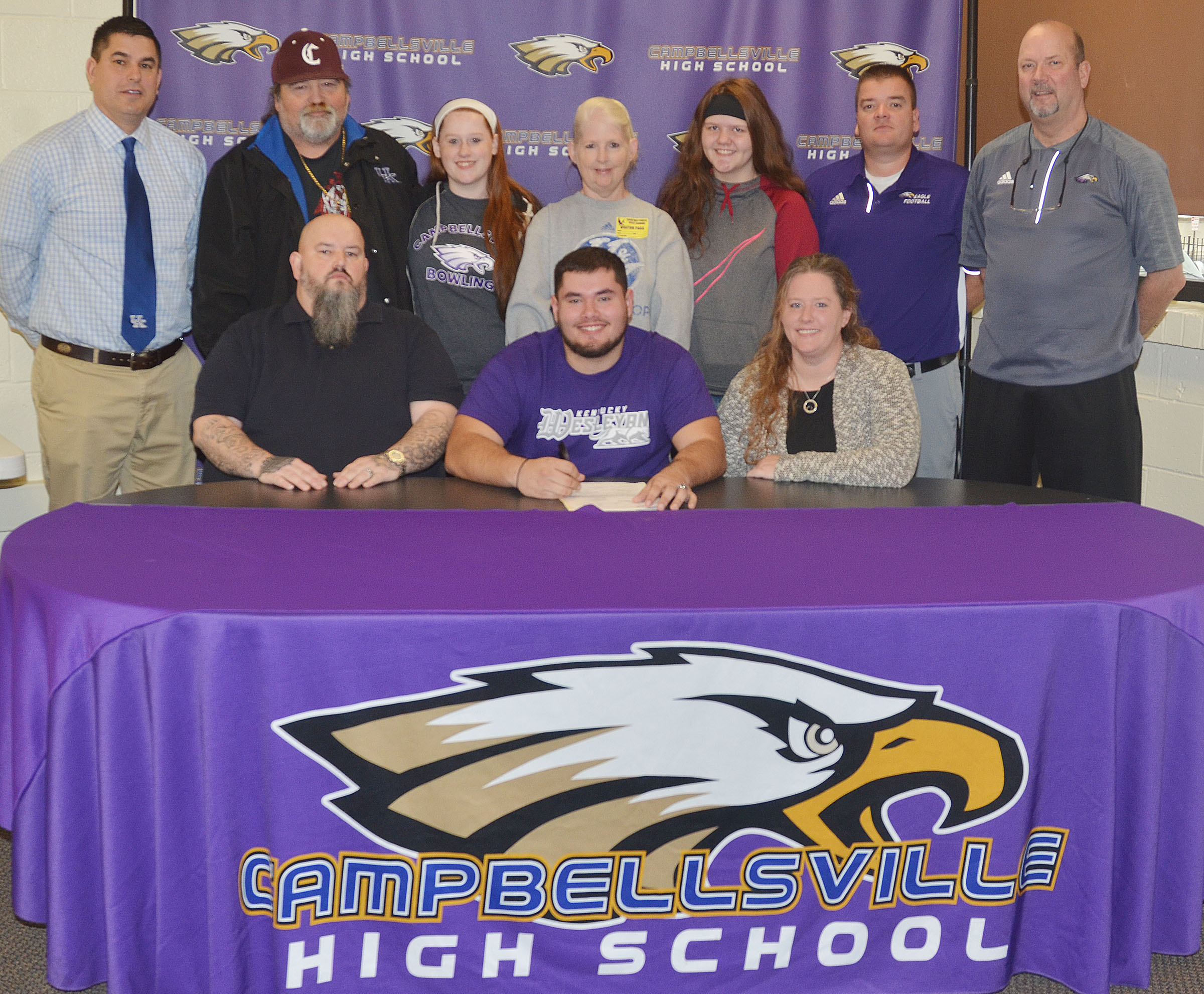 Campbellsville High School football player Logan Brown will continue his academic and football career at Kentucky Wesleyan College this fall. He officially signed his letter of intent on Wednesday, Feb. 1, which was National Signing Day. From left, front, are stepfather Johnny Welch, Logan, and his mother, Krissy Welch. Back, CHS Principal Kirby Smith, grandfather Joe Pendleton, sister and CHS sophomore Gracie Miller, grandmother Kim Pendleton, sister and Campbellsville Middle School seventh-grader Autumn Brown, CHS head football coach Dale Estes and CHS Athletic Director Tim Davis.