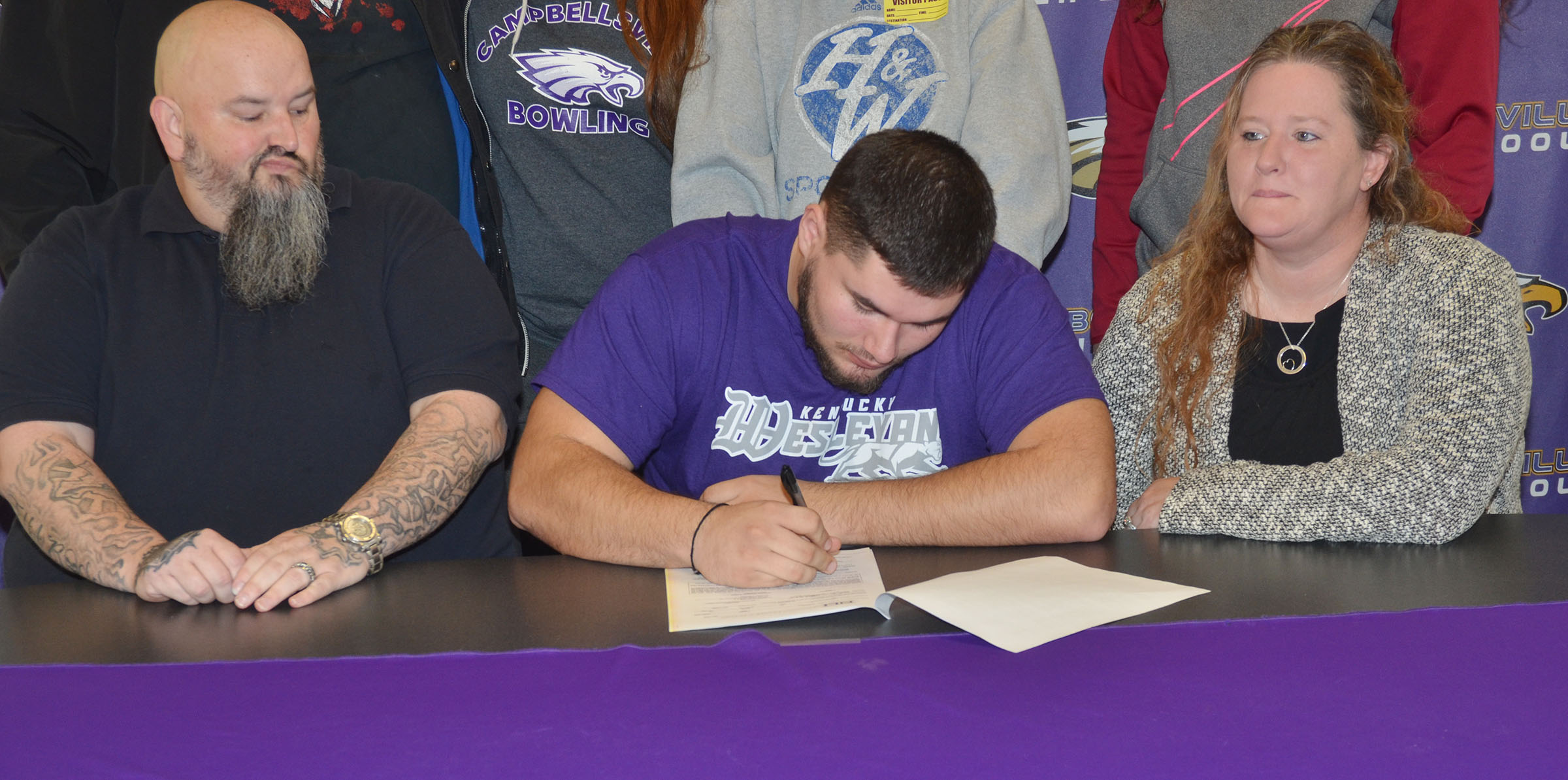 Campbellsville High School football player Logan Brown will continue his academic and football career at Kentucky Wesleyan College this fall. He officially signed his letter of intent on Wednesday, Feb. 1, which was National Signing Day. From left are stepfather Johnny Welch, Logan, and his mother, Krissy Welch.