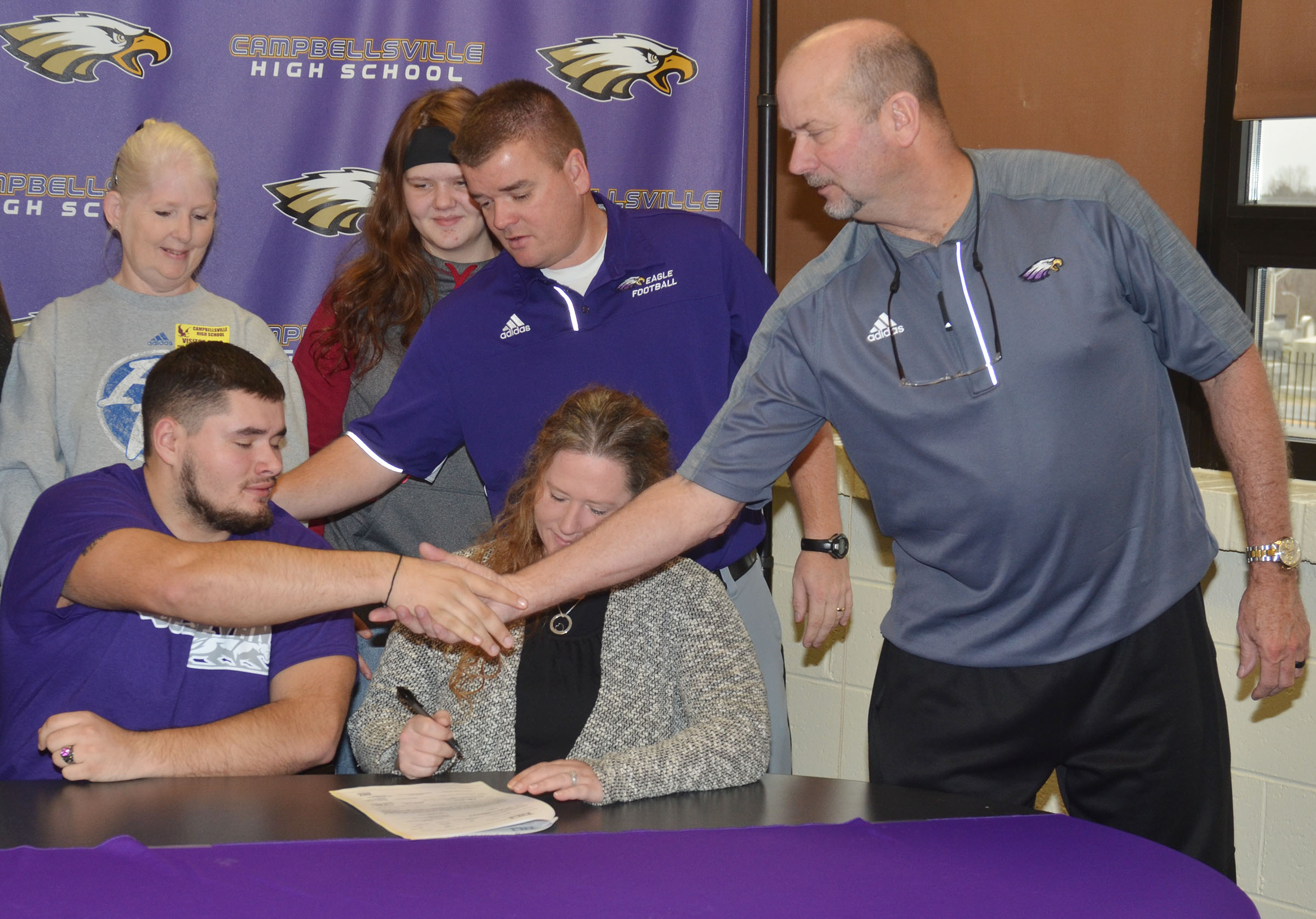 Campbellsville High School football player Logan Brown will continue his academic and football career at Kentucky Wesleyan College this fall. He officially signed his letter of intent on Wednesday, Feb. 1, which was National Signing Day. Above, Brown receives congratulations from CHS head football coach Dale Estes, at left, and CHS Athletic Director Tim Davis.